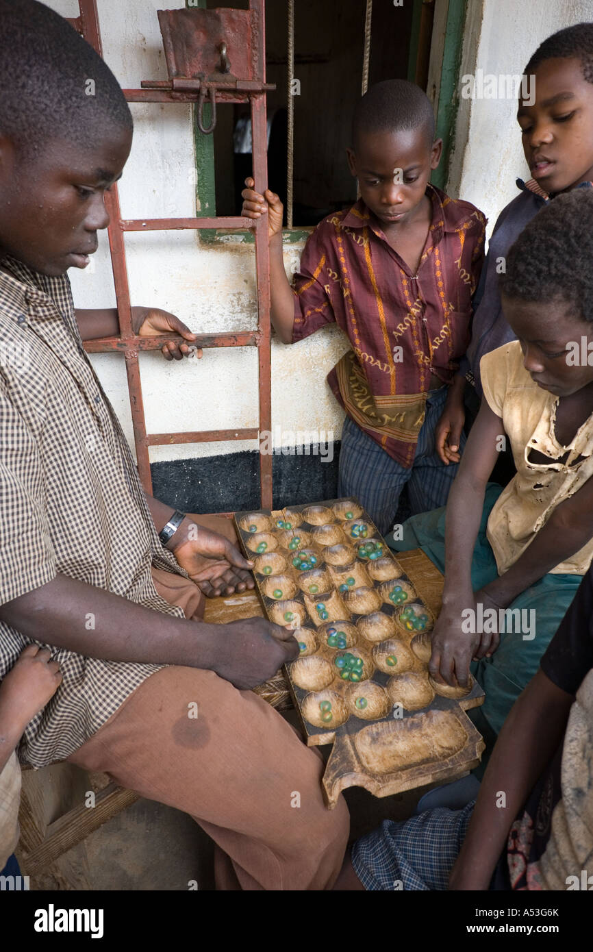 Playing A Game Of Bawo Mancala Outside The Grocery Shop
