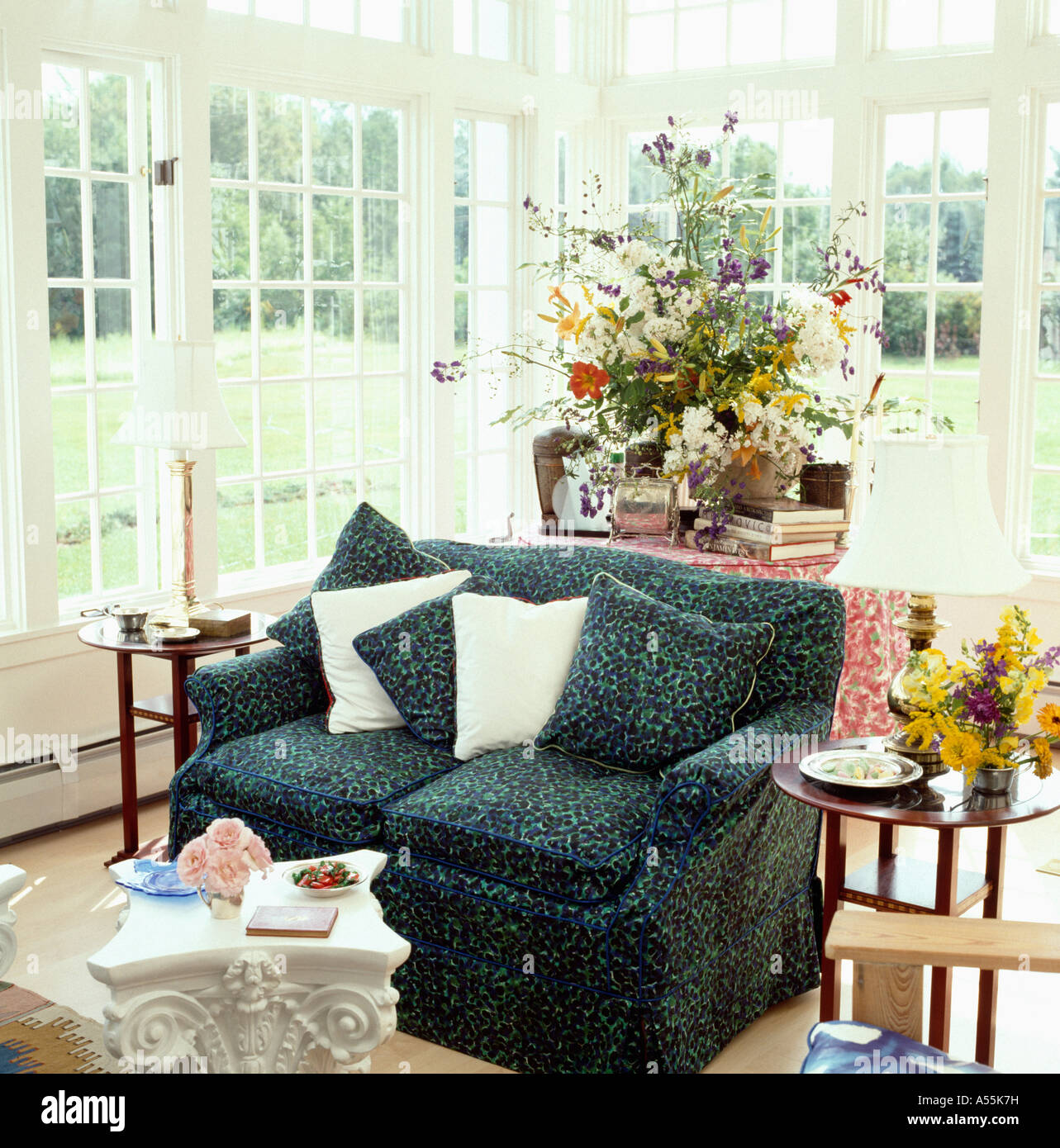 Dark green patterned sofa in conservatory sittingroom with view of ...