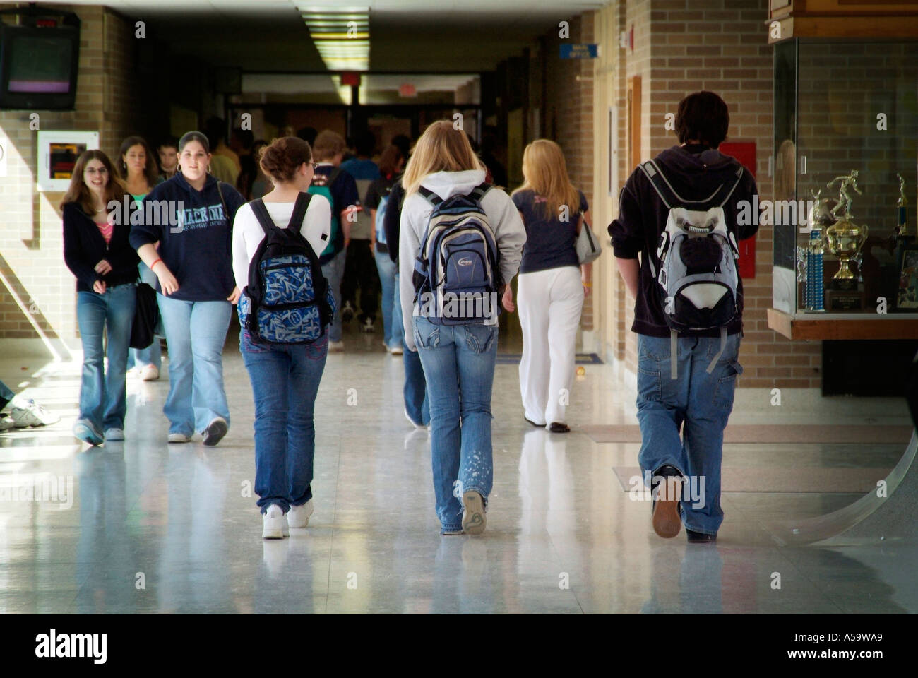 High school students with backpacks walk in hall during passing of ...
