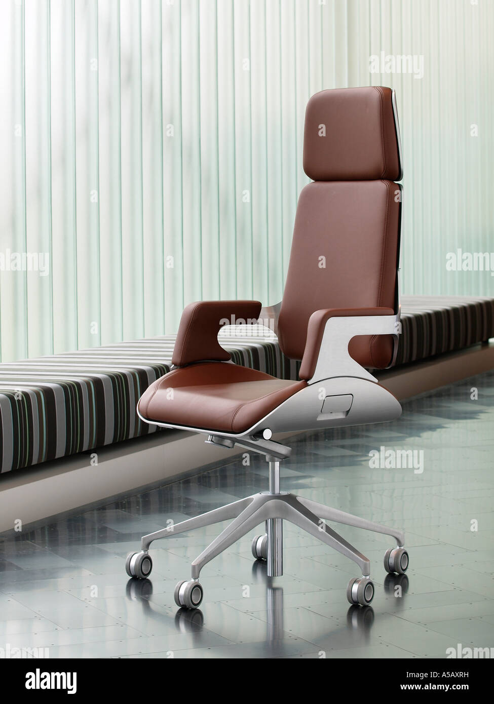 Brushed metal and brown leather luxury office chair on dark steel ...