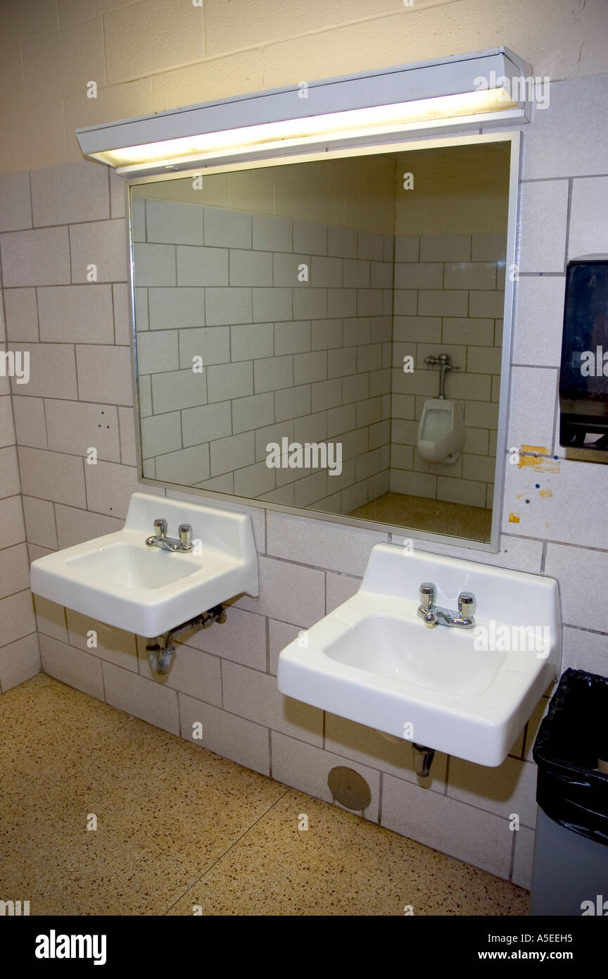 Public restroom  bathroom  2 sinks  mirror  flourescent lights  urinal   white tile. Public restroom  bathroom  2 sinks  mirror  flourescent lights