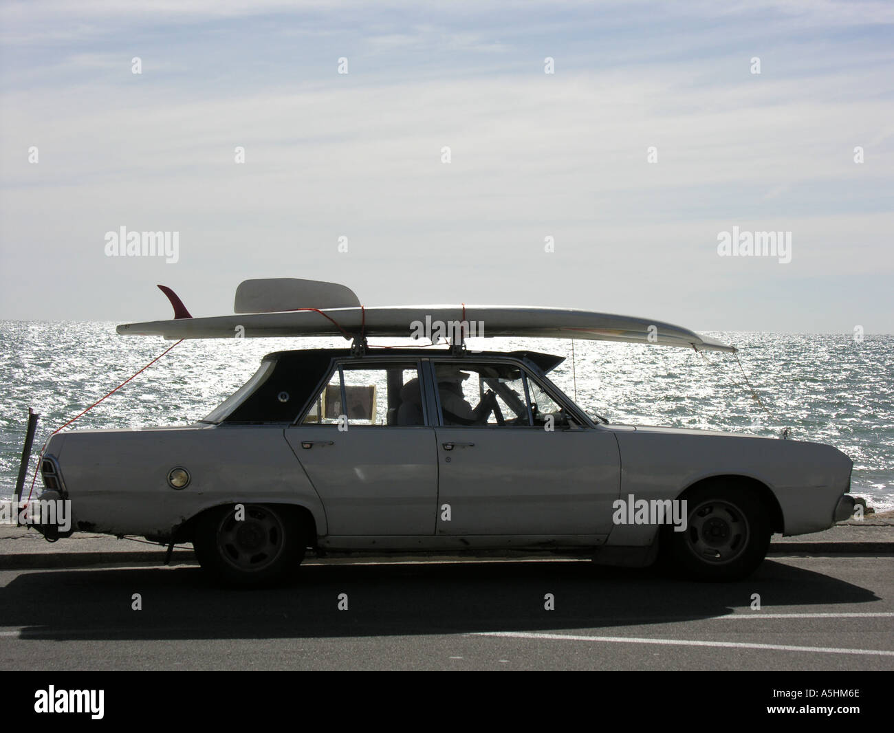 Old convertible car with surfboard on roof driving on esplanade ...