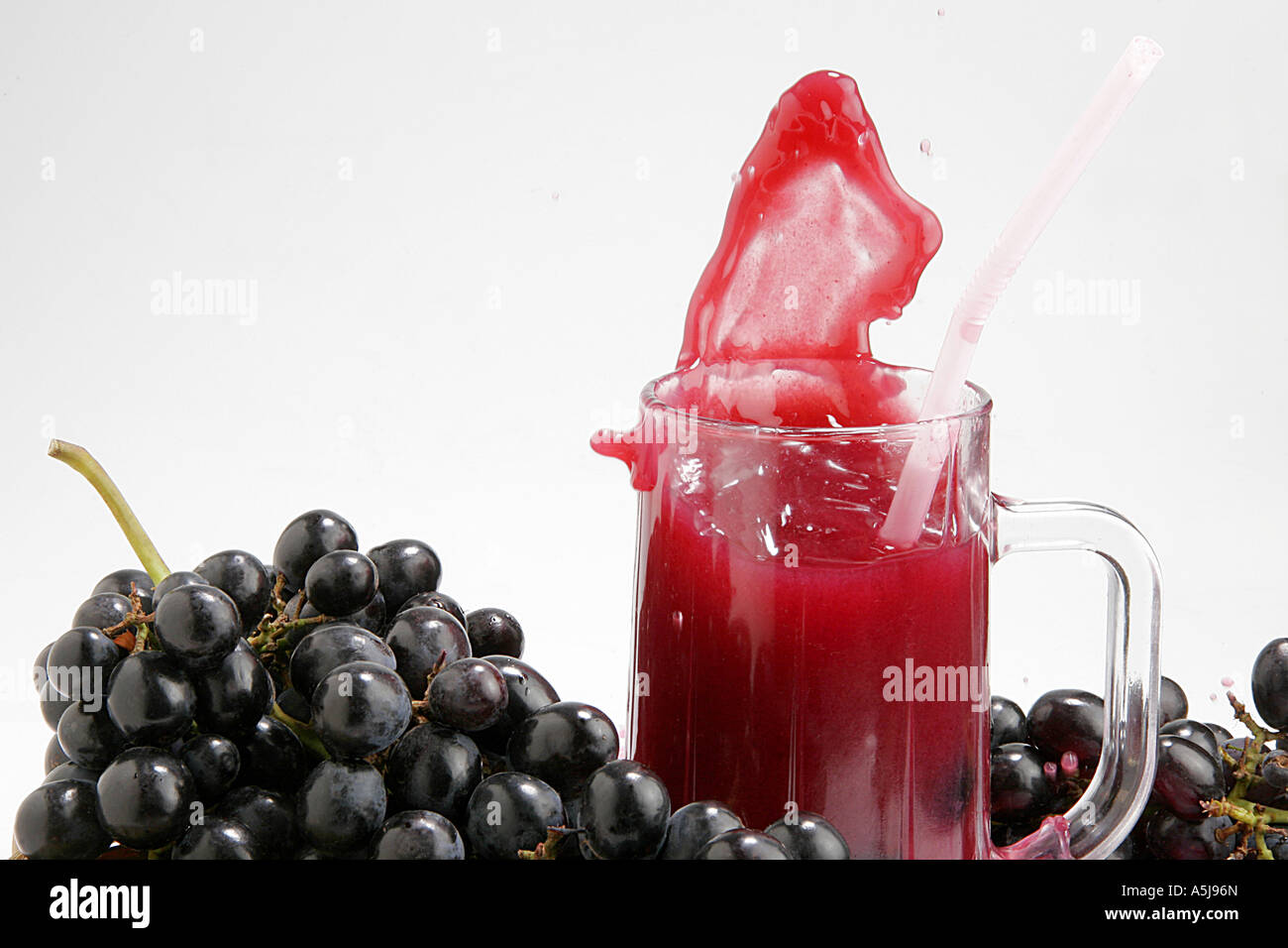 fruit black grapes glass juice splash white background