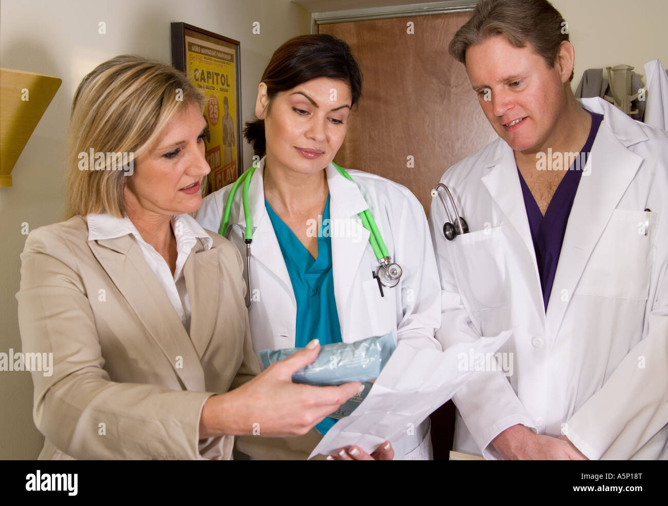 drug rep explains new drugs to two doctors stock photo royalty drug rep explains new drugs to two doctors