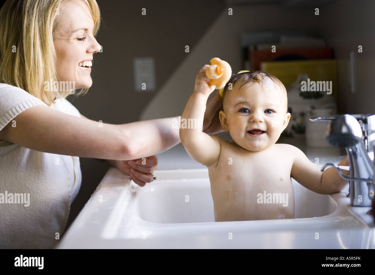 Woman bathing baby in sink Stock Photo, Royalty Free Image ...