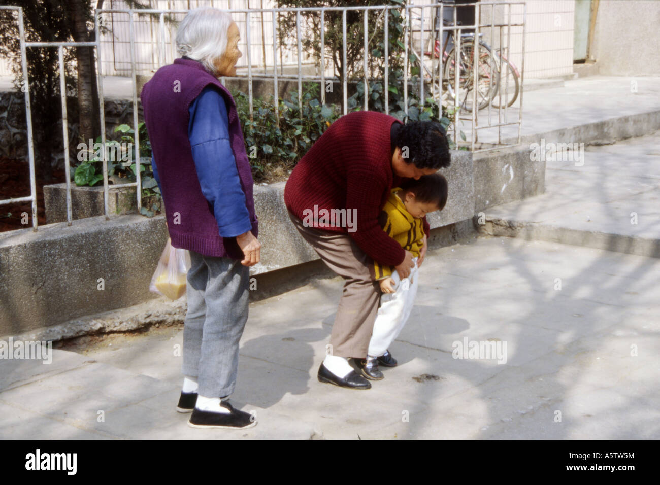 PEE ON ALLSITUATION IN CHINA Grandmother looks on as her daughter helps her young son to urinate in the  street,
