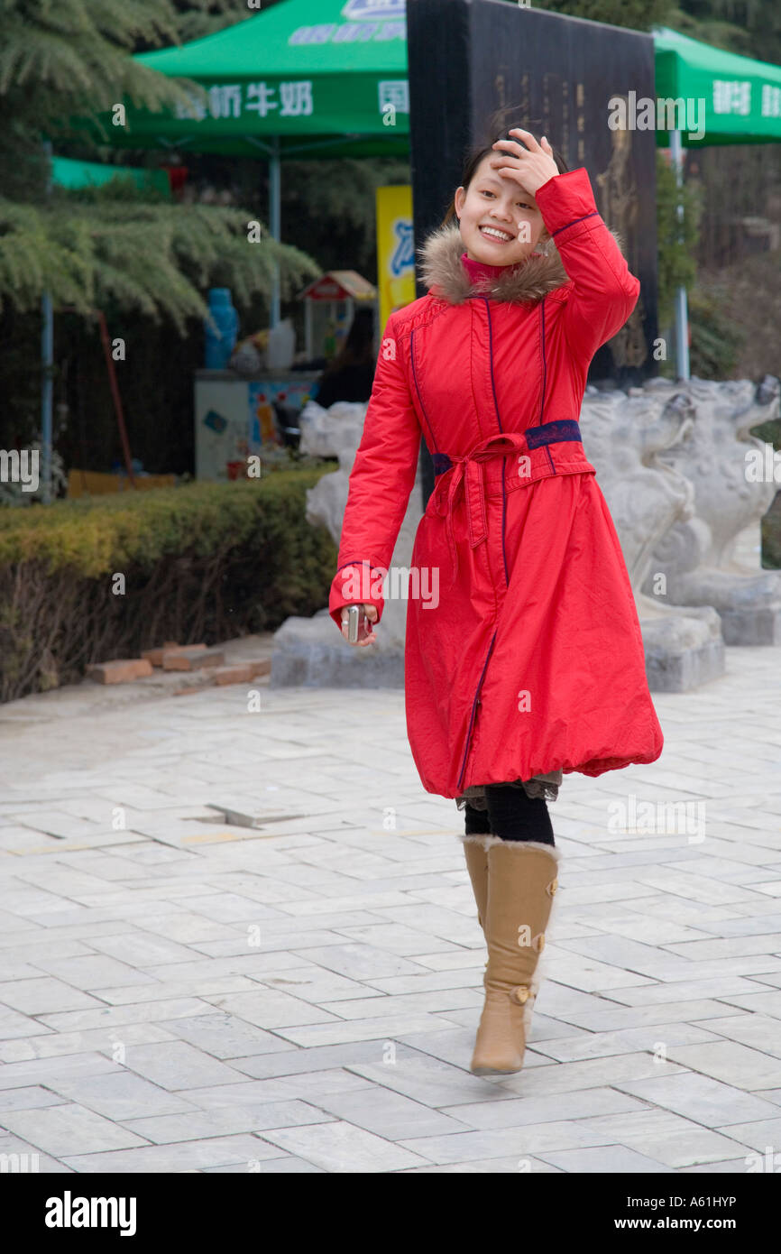 Beautiful young modern Chinese woman in red coat walking towards ...