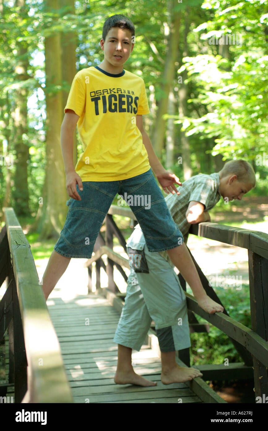 Two Young Boys Barefoot On A Wooden Bridge In A Forest