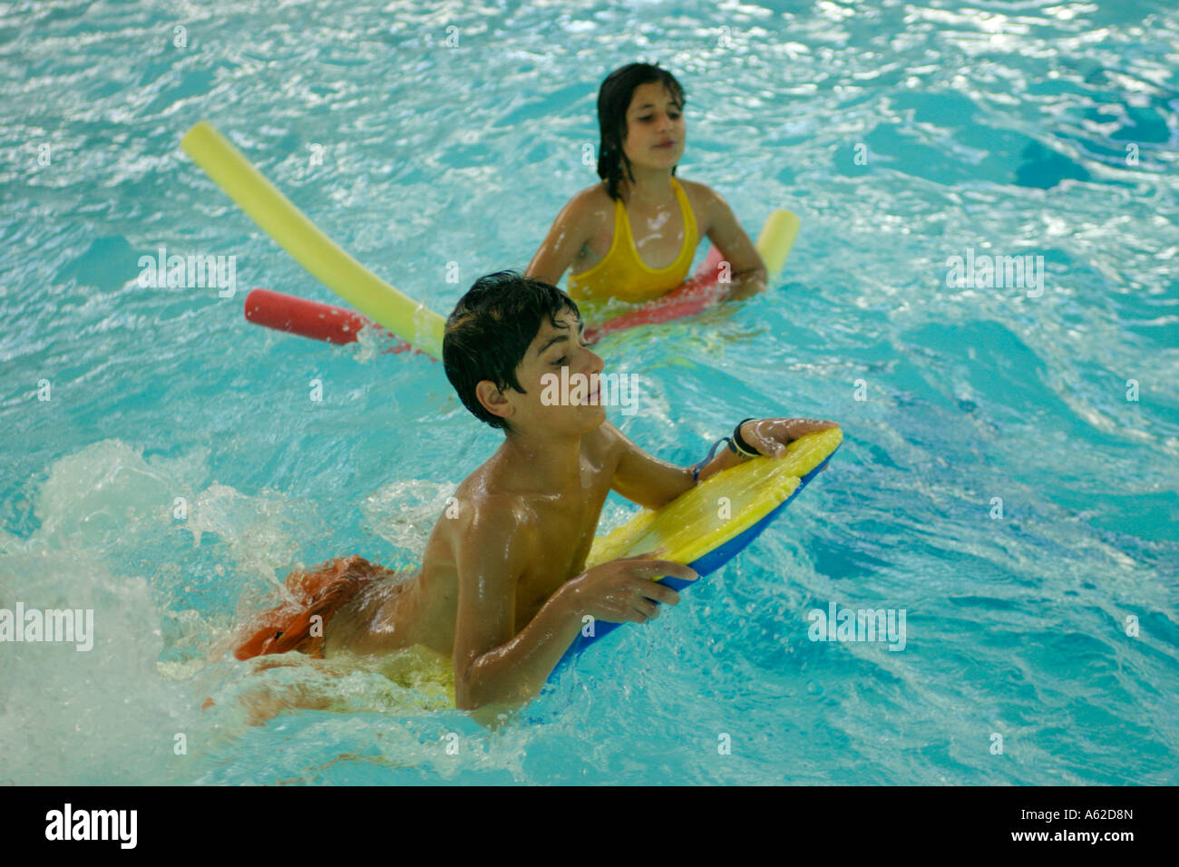 children with floatation devices at an indoor swimming pool stock photo royalty free image
