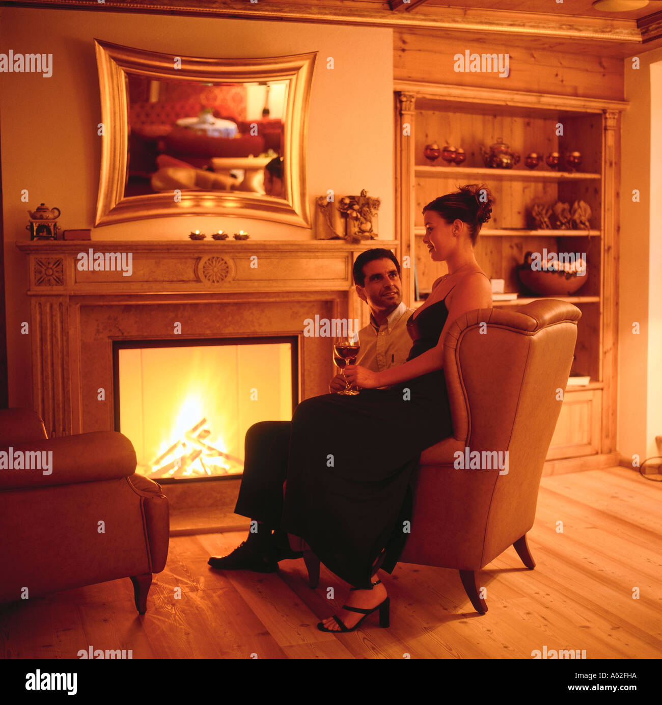 Couple sitting in front of chimney Stock Photo, Royalty Free Image ...