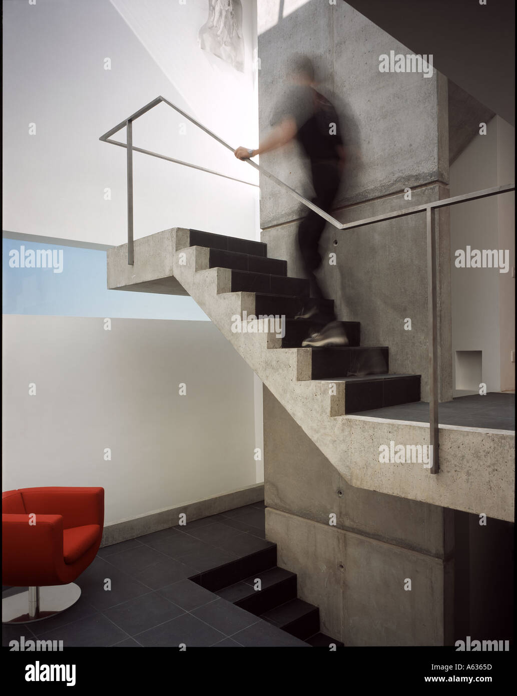 The Tall House Interior Of The Stair Well With Red Chair And Blurred Man On  The Stairs. Architect: Terry Pawson Architects