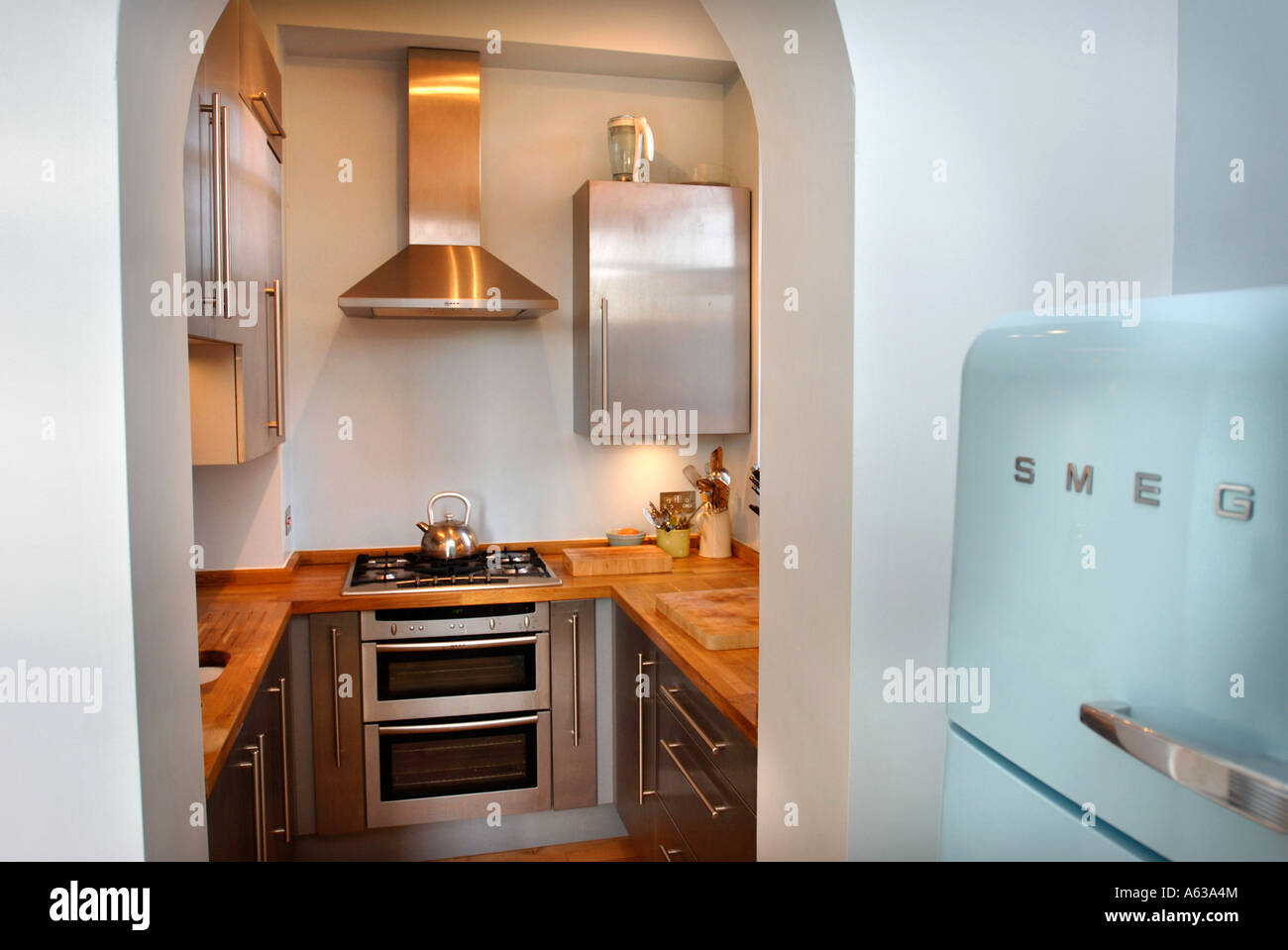 a small fitted kitchen with a smeg fridge uk stock image