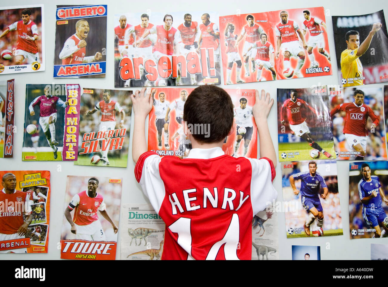 Bedroom wall with posters - Stock Photo Young Arsenal Football Supporter Boy Putting Up Posters On His Bedroom Wall London England Uk