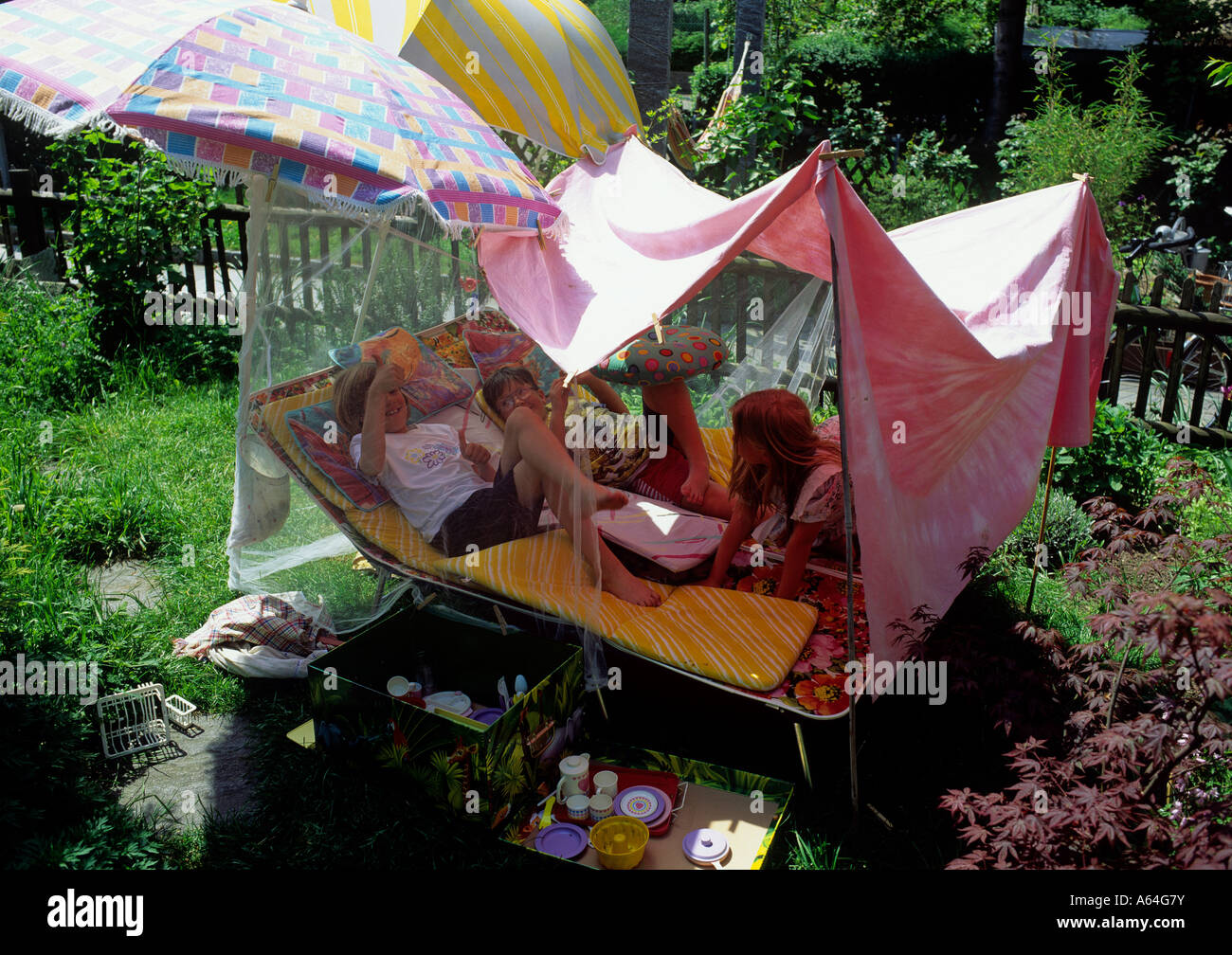 infants playing in selfmade tent adventure backyard holidays stock