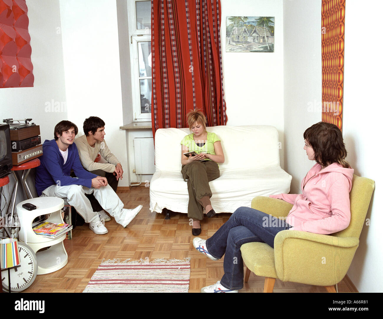 group of teenage friends sitting together in living room Stock