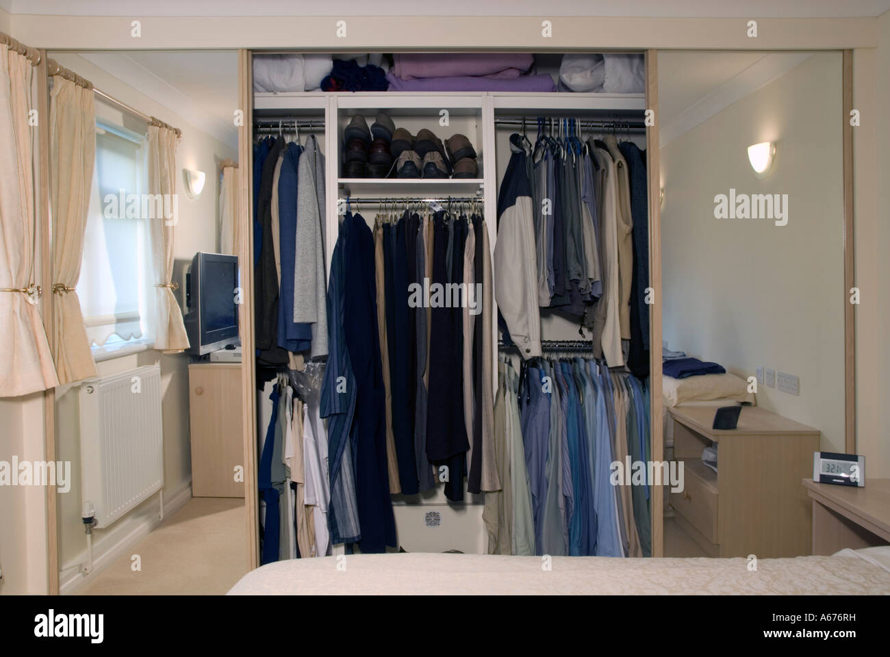 Shared Built In Bedroom Wardrobe With Mirror Sliding Doors Open To Show Garments On Hanging Rail Reflections Of Room Interior