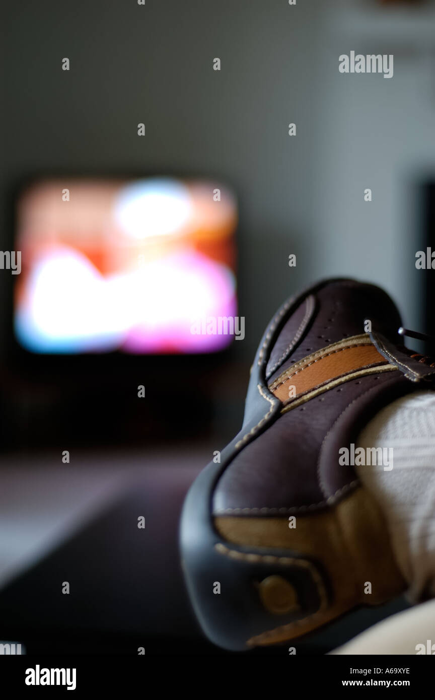 Man watching tv with feet on coffee table stock photo royalty man watching tv with feet on coffee table geotapseo Gallery