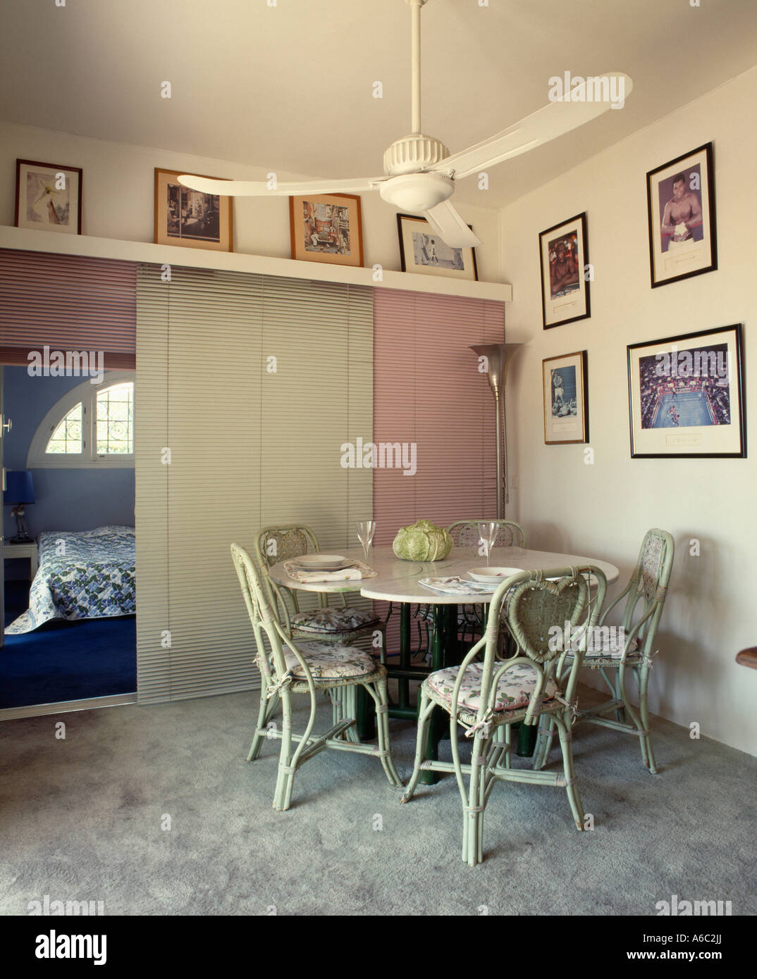 Ceiling Fan Above Circular Table In Dining Room With Pictures On Walls And Sliding Door To Bedroom