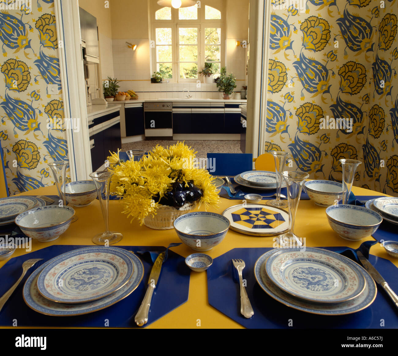 Delightful Blue Napkins And Crockery On Yellow Tablecloth In Diningroom With Yellow  And Blue Patterned Wallpaper And Open Door To Kitchen
