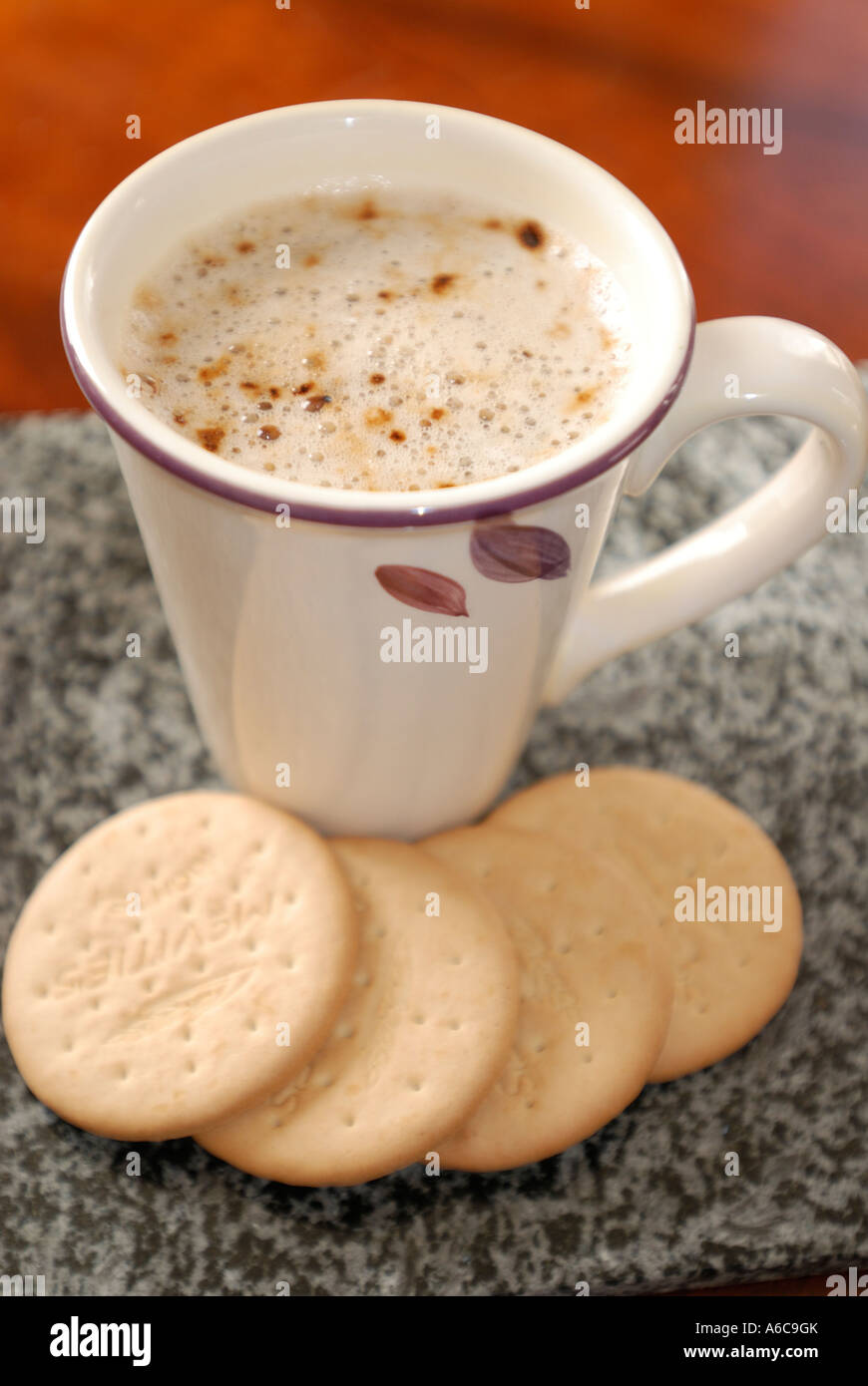 Cup Of Frothy Coffee With Four Plain Rich Tea Biscuits