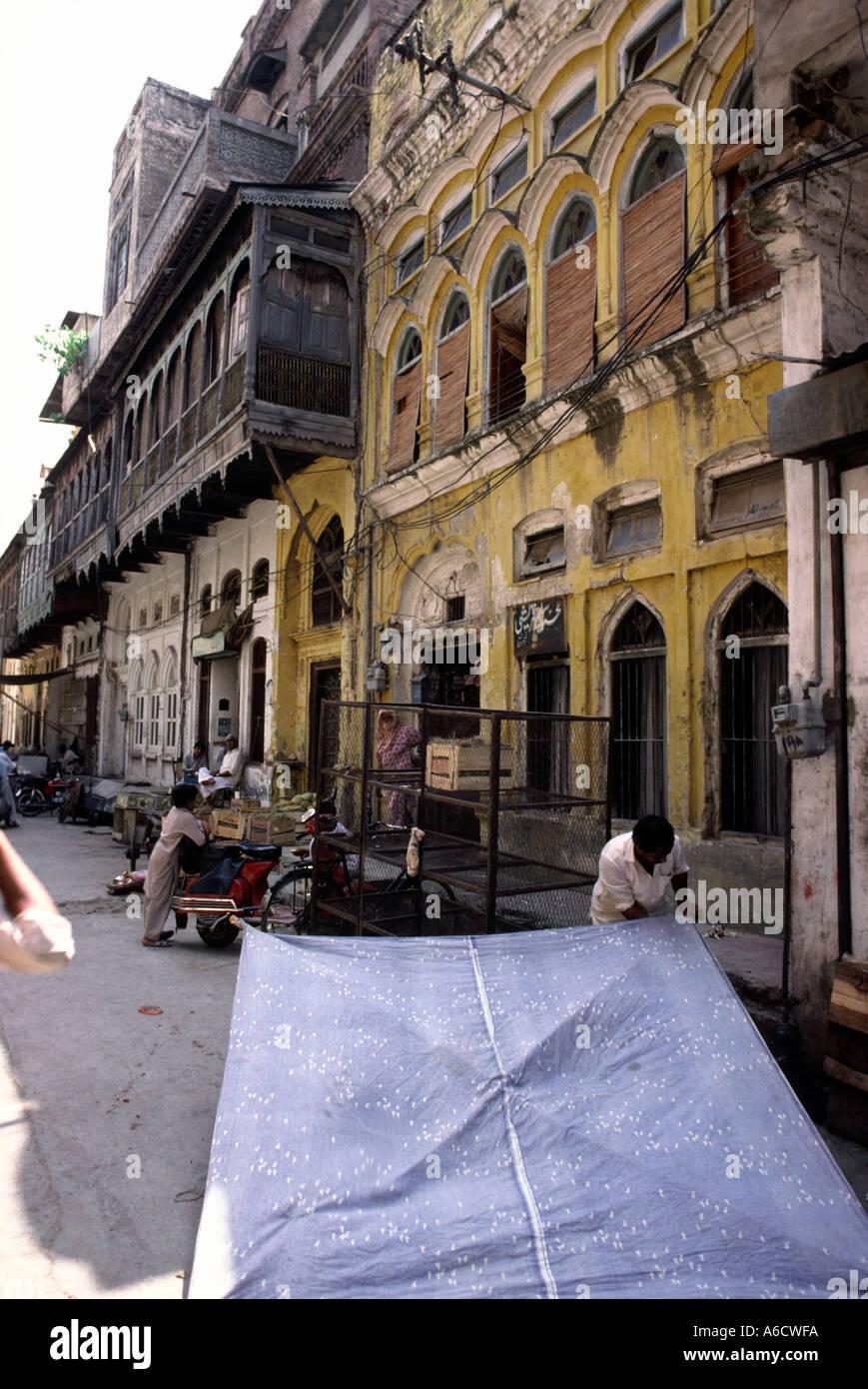 Pakistan Rawalpindi Rajah Bazaar Man Erecting Awning Amongst Old Houses