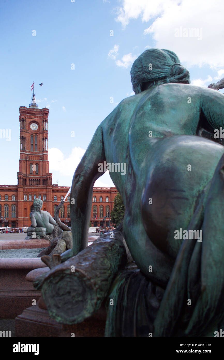Stock photo sculpture of the neptun fountain in the middle district of berlin germany red house in the background