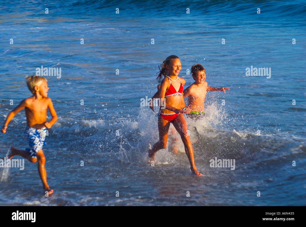 Kids Playing At The Beach Running In Water