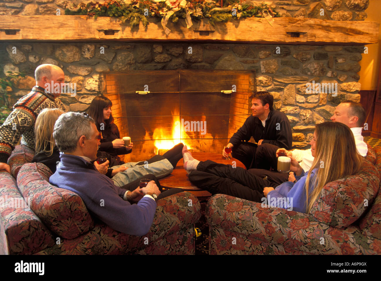 group of friends relaxing apres ski in front of a roaring log fire