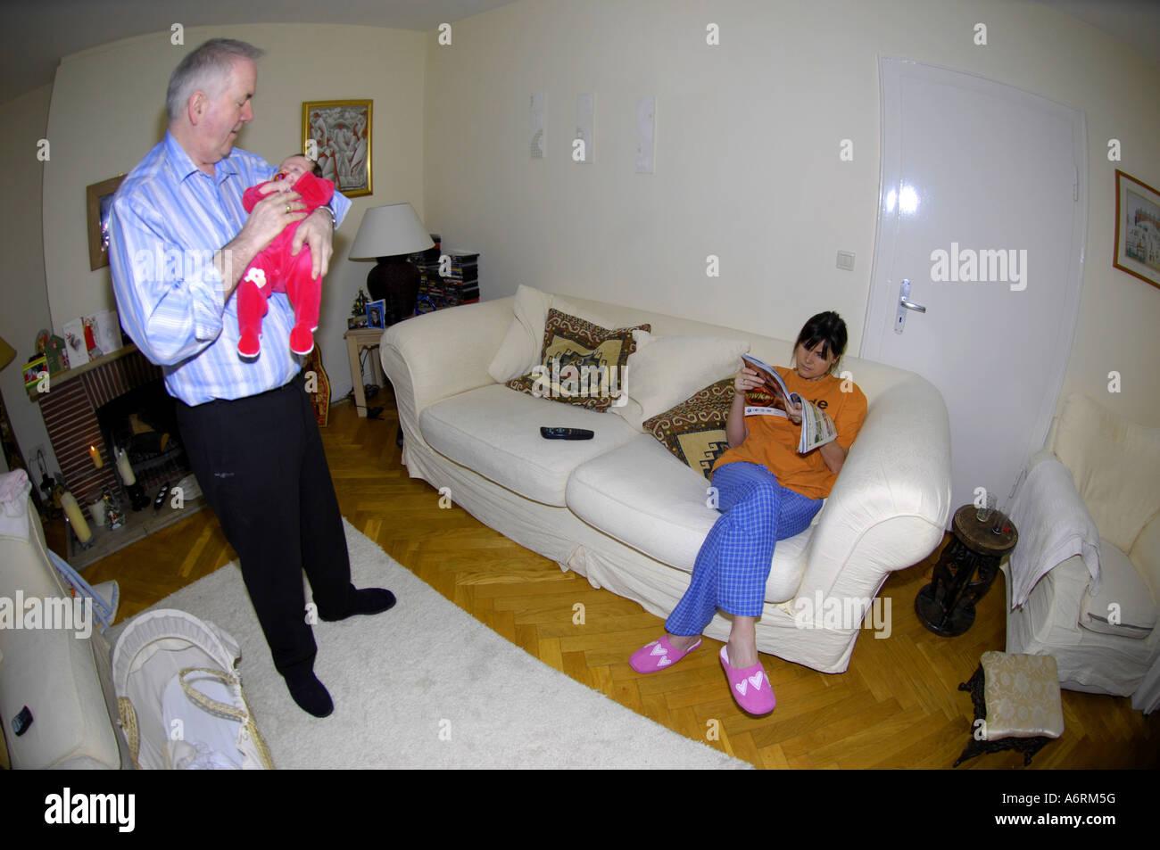 stock photo single mother baby home inside motherhood parent sit setee sofa couch care caring grandad gradfather rooom lounge