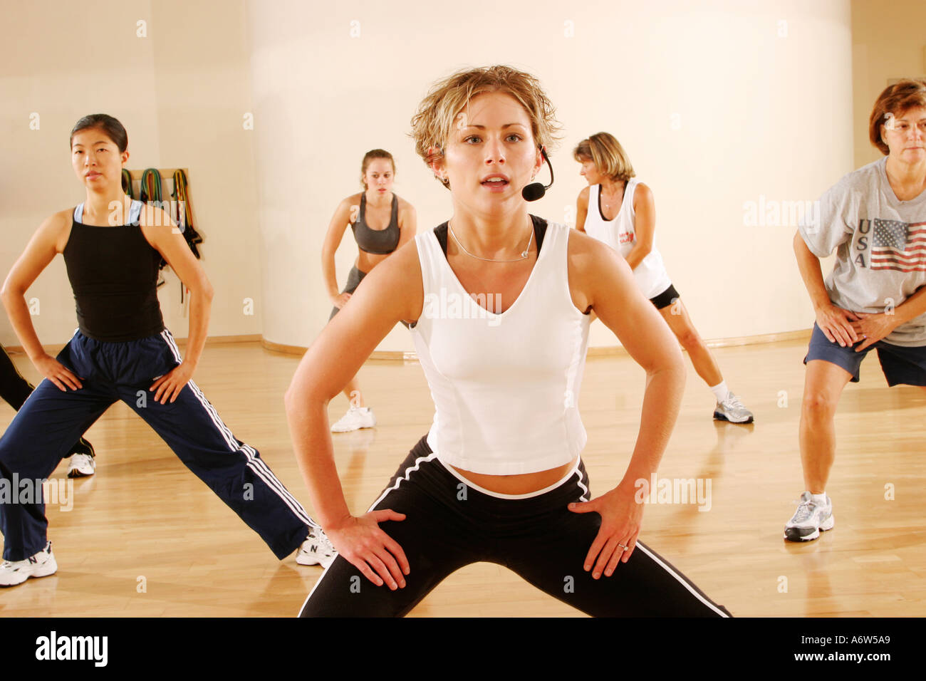 a kickboxing or aerobics class in a studio led by a blonde female ...