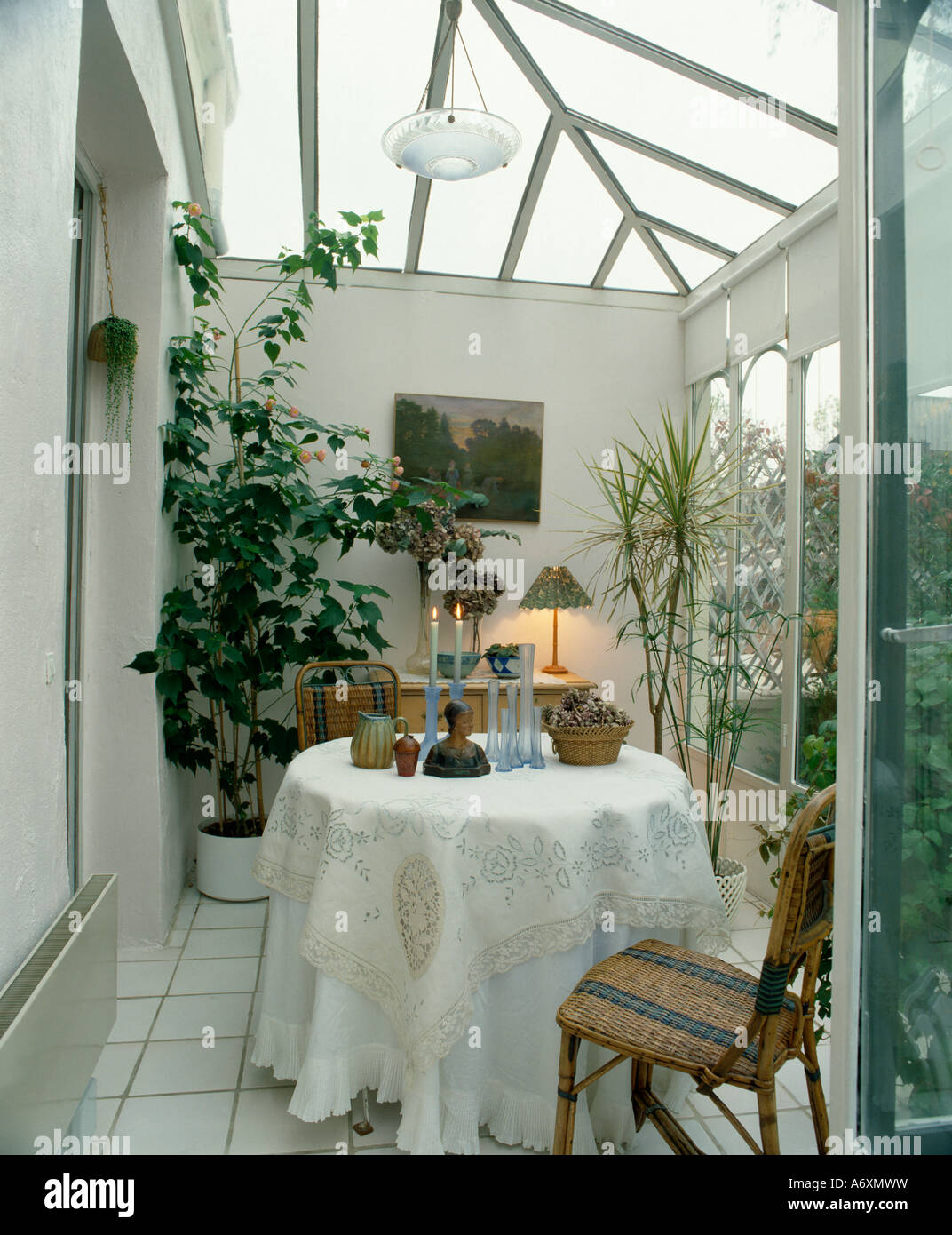 Dining Table With White Cloth In Modern Glass Conservatory Extension Tiled Floor And Large Houseplants