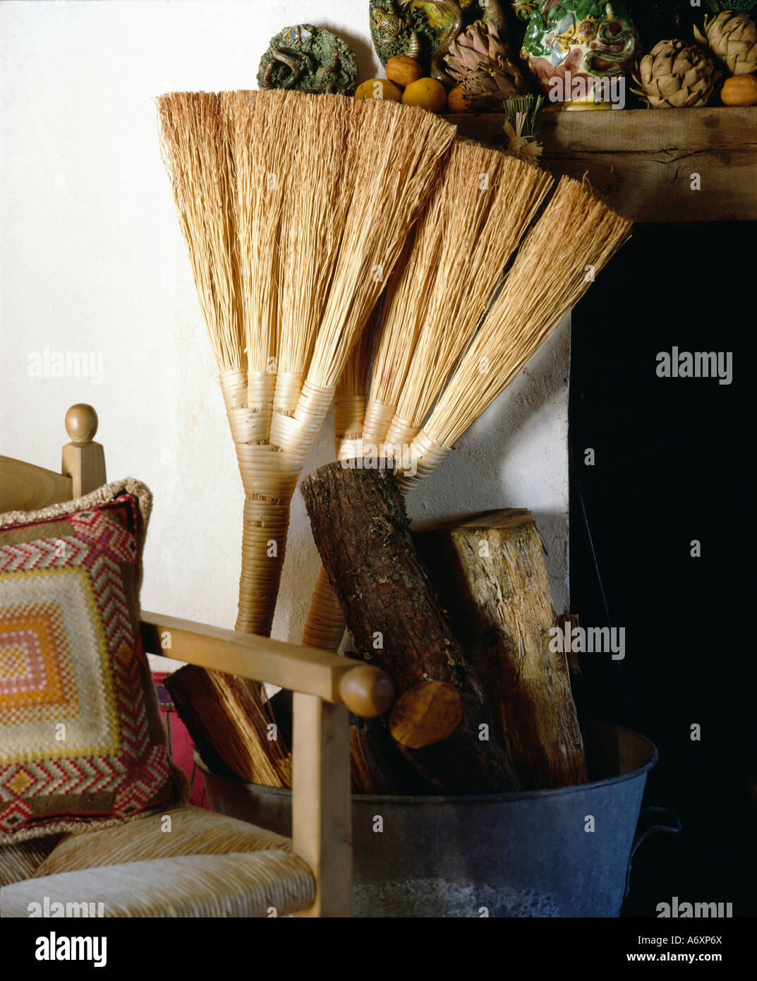 Wooden armchair with cushion - Close Up Of Two Rustic Brooms Beside Pile Of Logs And Wooden Armchair With Ethnic Cushion