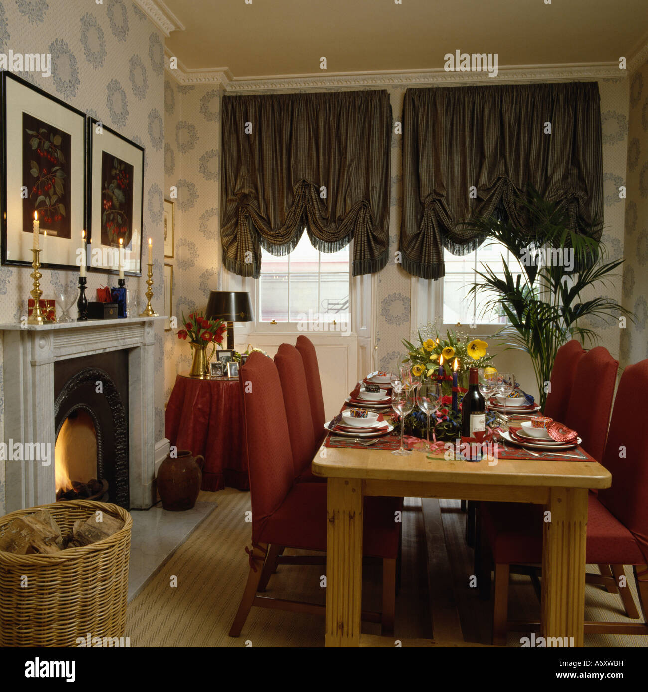 Diningroom With Festoon Blinds And Table Upholstered Red Chairs In Front Of Fireplace