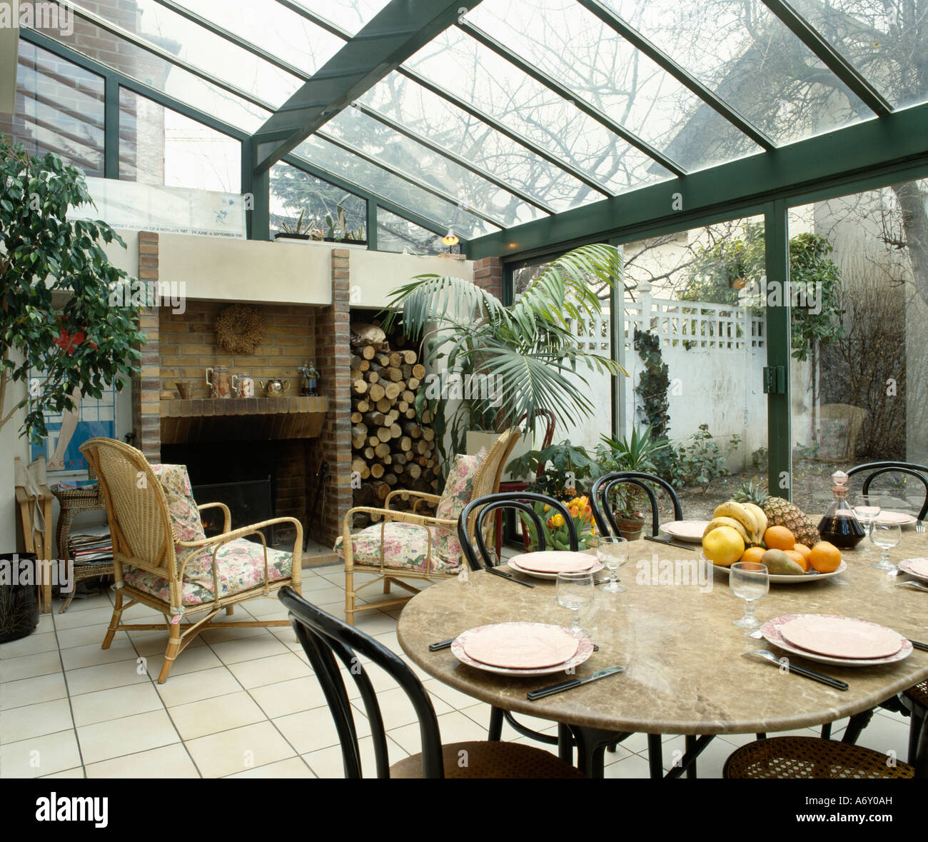 Dining Table And Fireplace In Glass Conservatory Extension