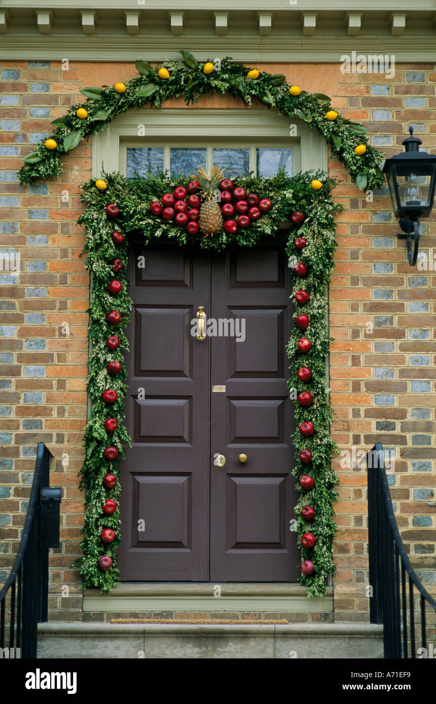 Close Up Of A Front Door With A Holiday Garland Of Green Leaves Red Apples  Yellow Lemons And A Pineapple