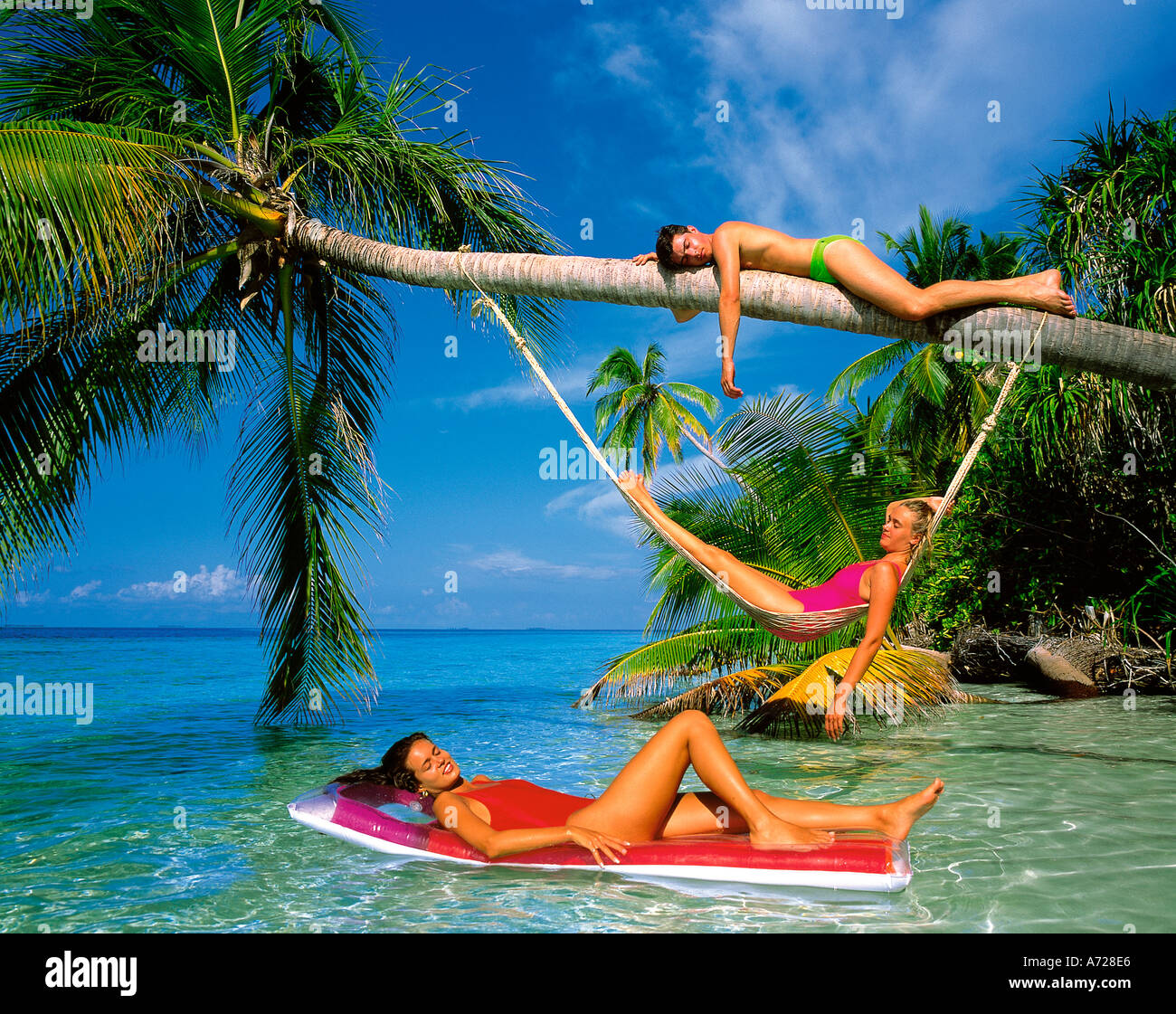 Group Of Three People Relaxing In Palm Trees On Tropical Beach Maldive Islands Indian Ocean