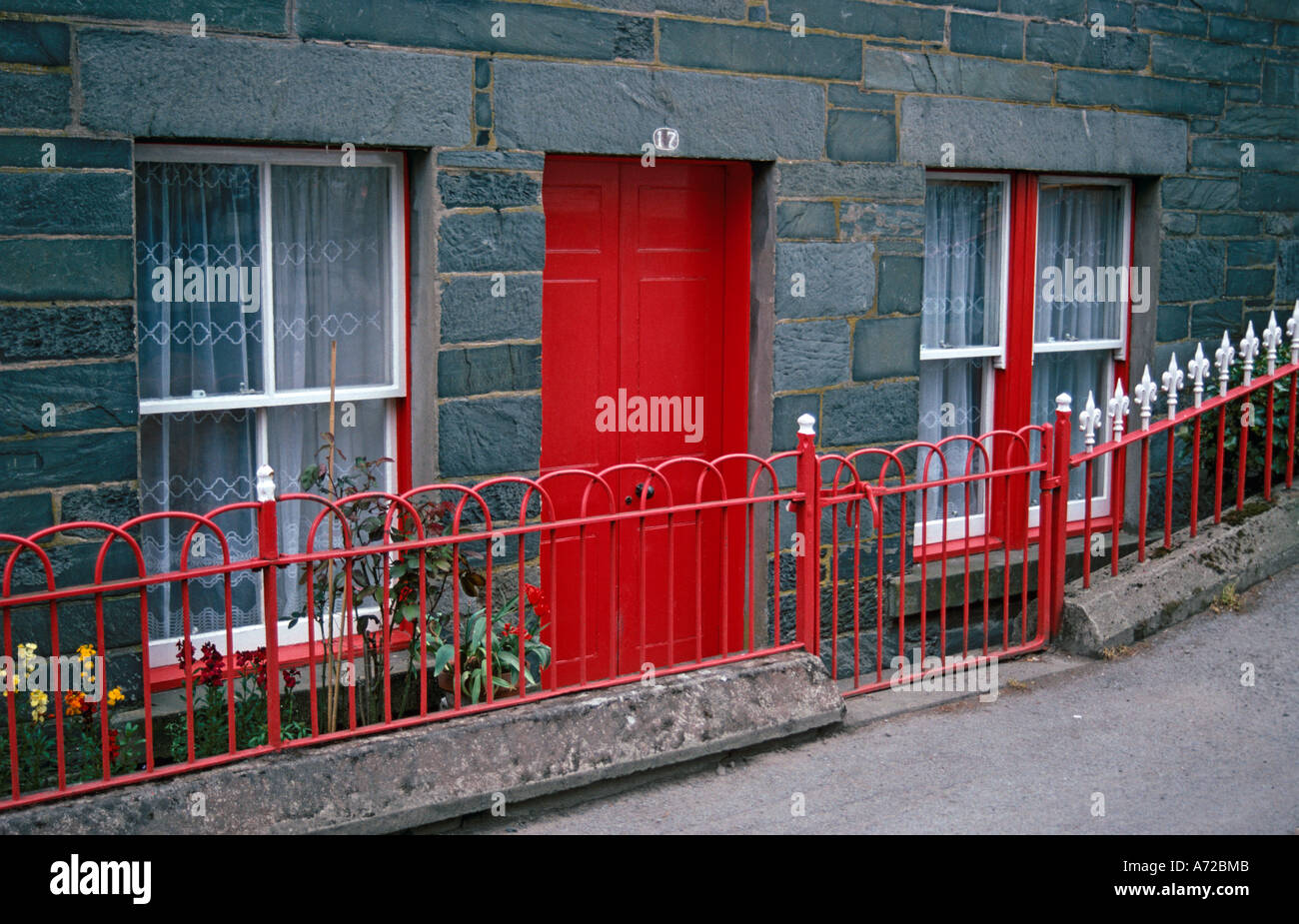 House built from grey blocks with bright red front door and railings. White painted sash windows with red surrounds & House built from grey blocks with bright red front door and ...