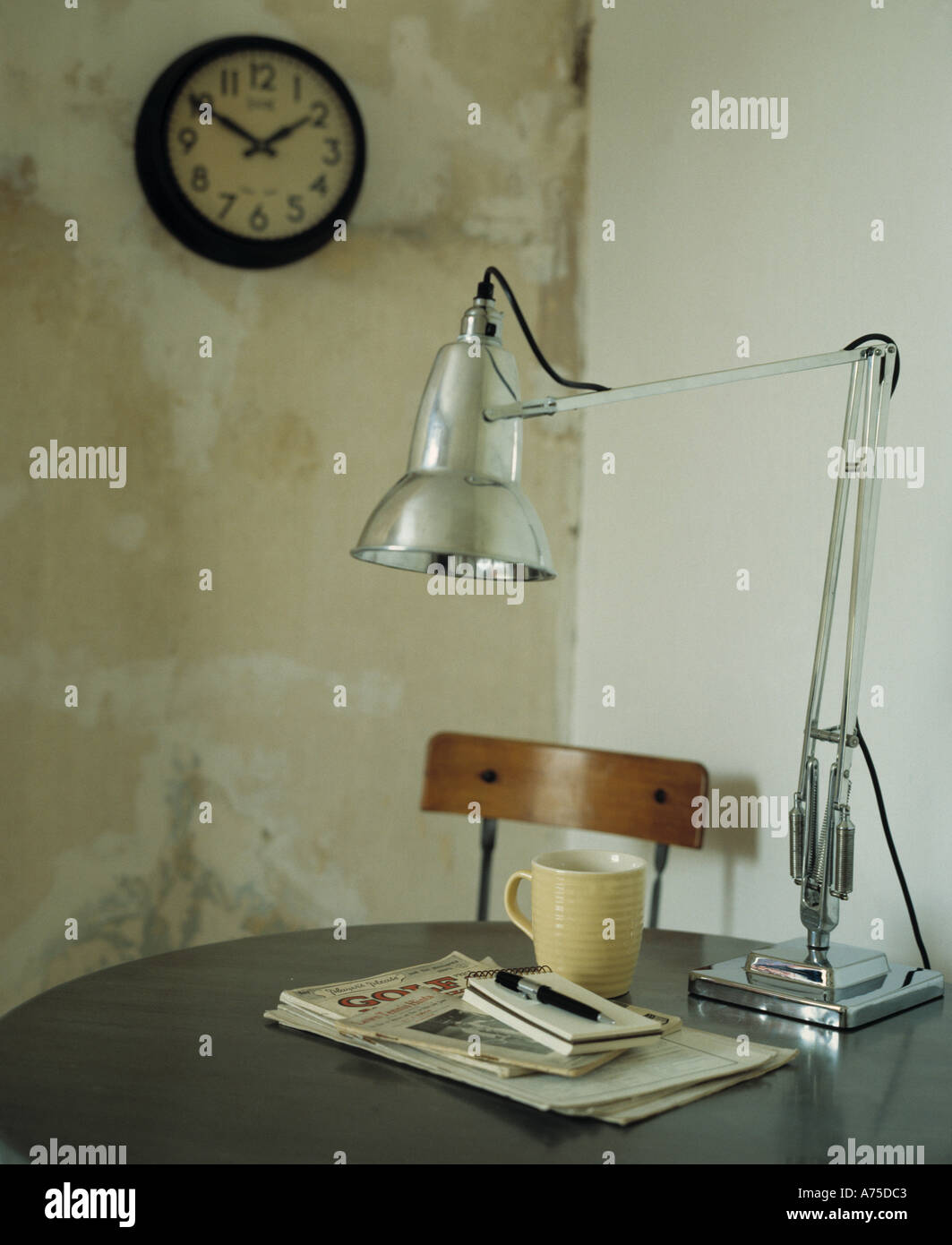 Close up of classic chrome anglepoise lamp on table with cup and close up of classic chrome anglepoise lamp on table with cup and notebooks in simple dining room with old circular clock on wall geotapseo Image collections