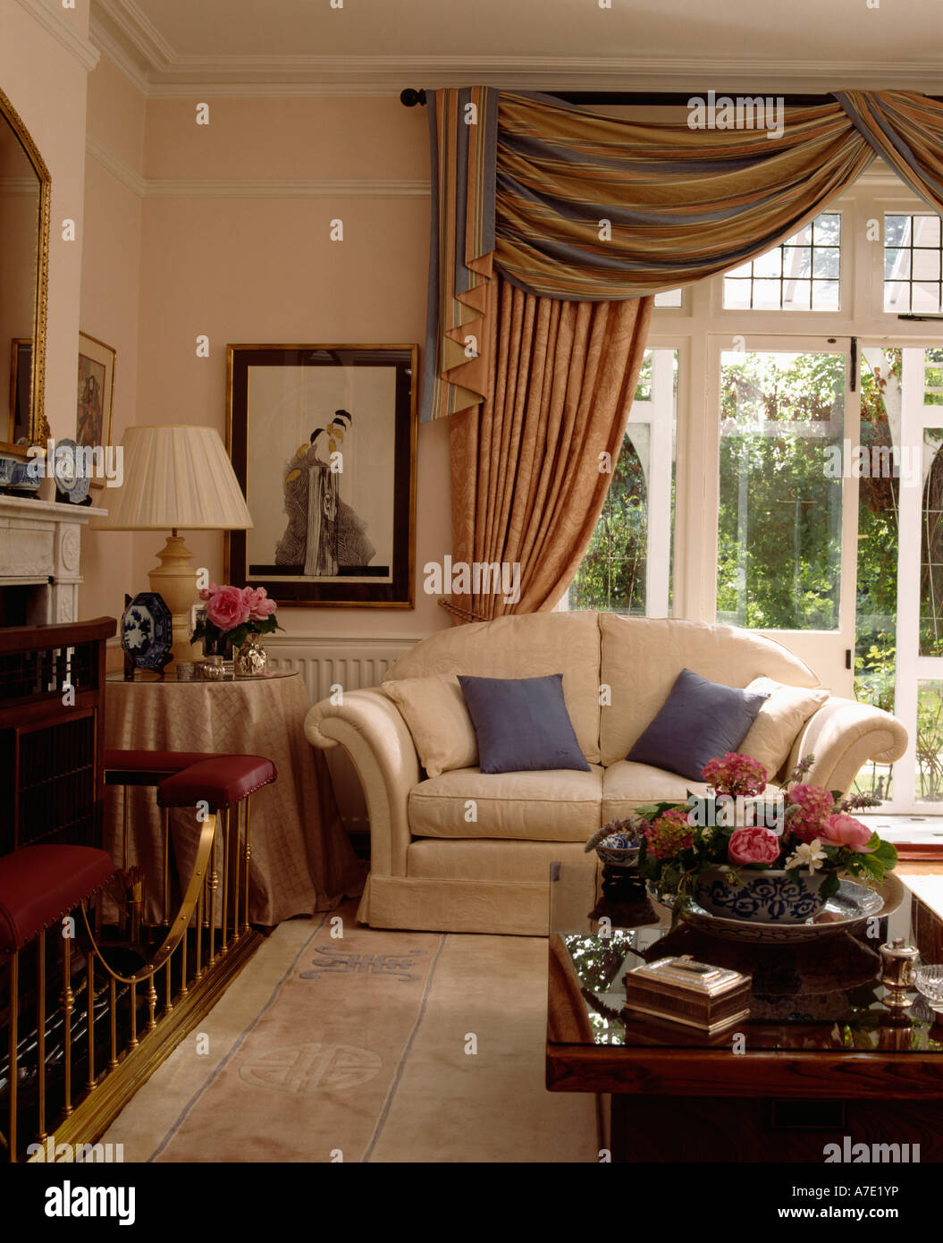Cream sofa with blue cushions in front of glass french for Cream french doors
