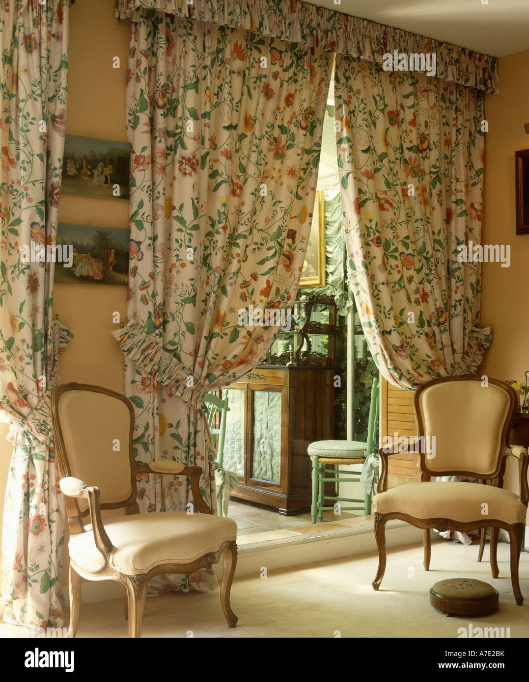 Cream Chairs In Front Of Floral Patterned Drapes At Doorway To Kitchen