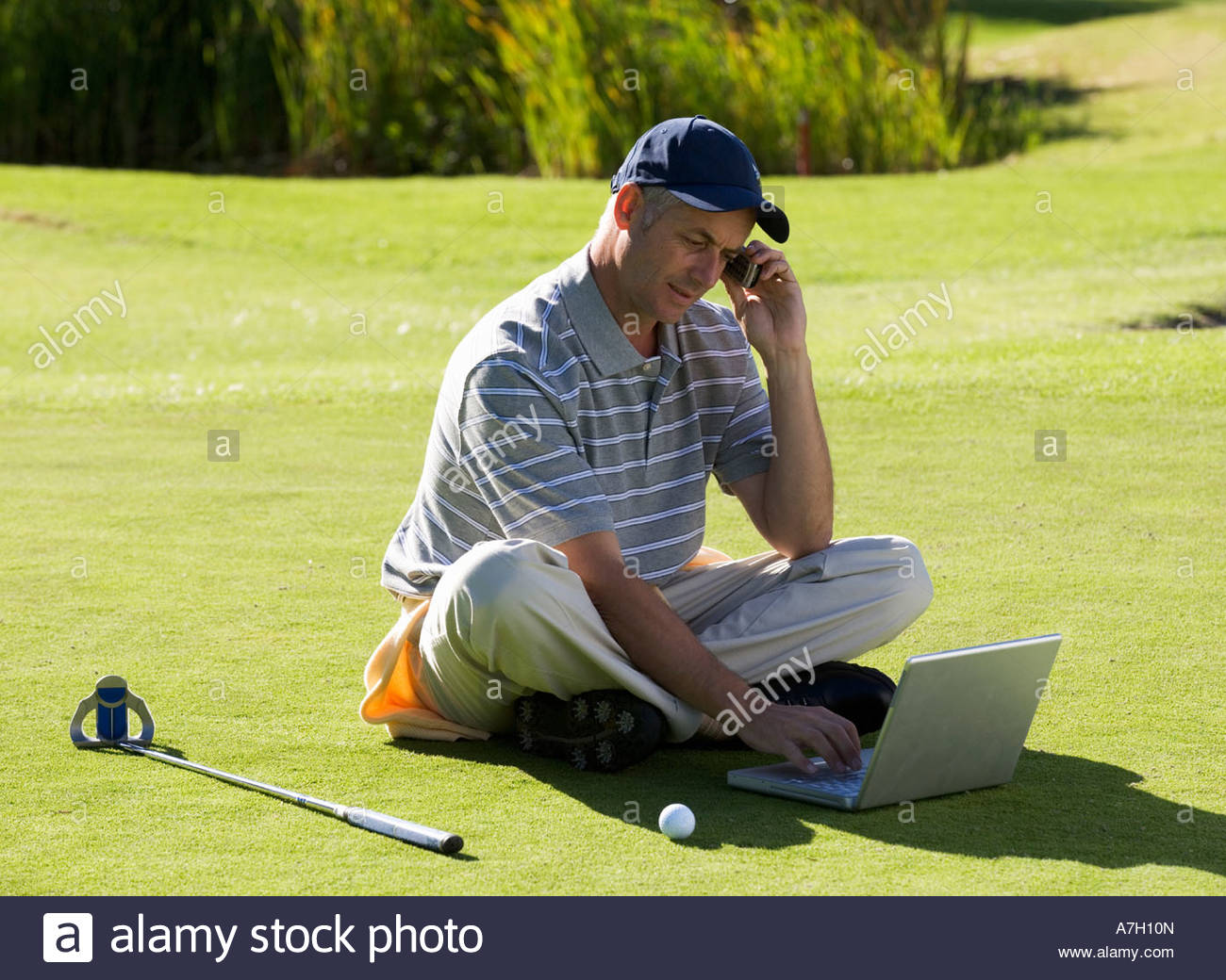 One Person Golf Cart >> Man using a laptop and mobile phone whilst on the golf course Stock Photo, Royalty Free Image ...