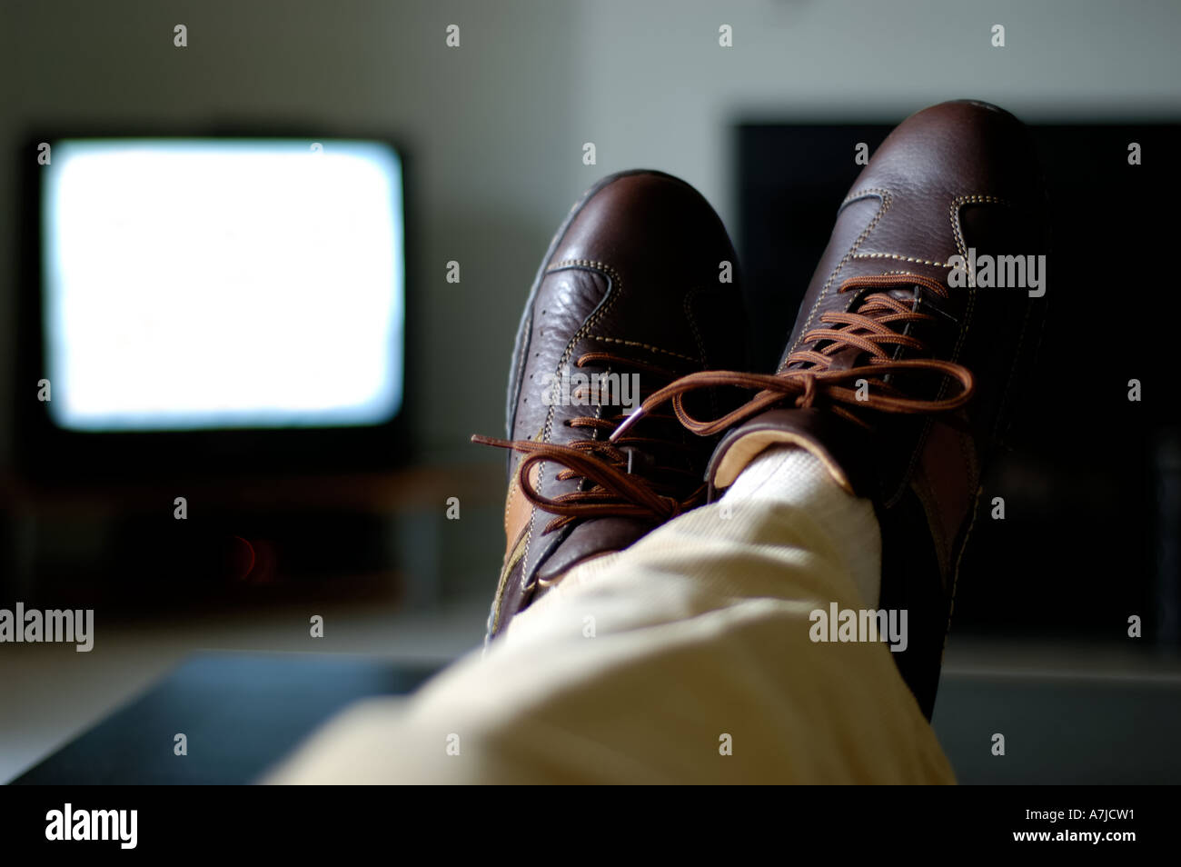 Man watching tv with feet on coffee table blank screen stock photo man watching tv with feet on coffee table blank screen geotapseo Choice Image