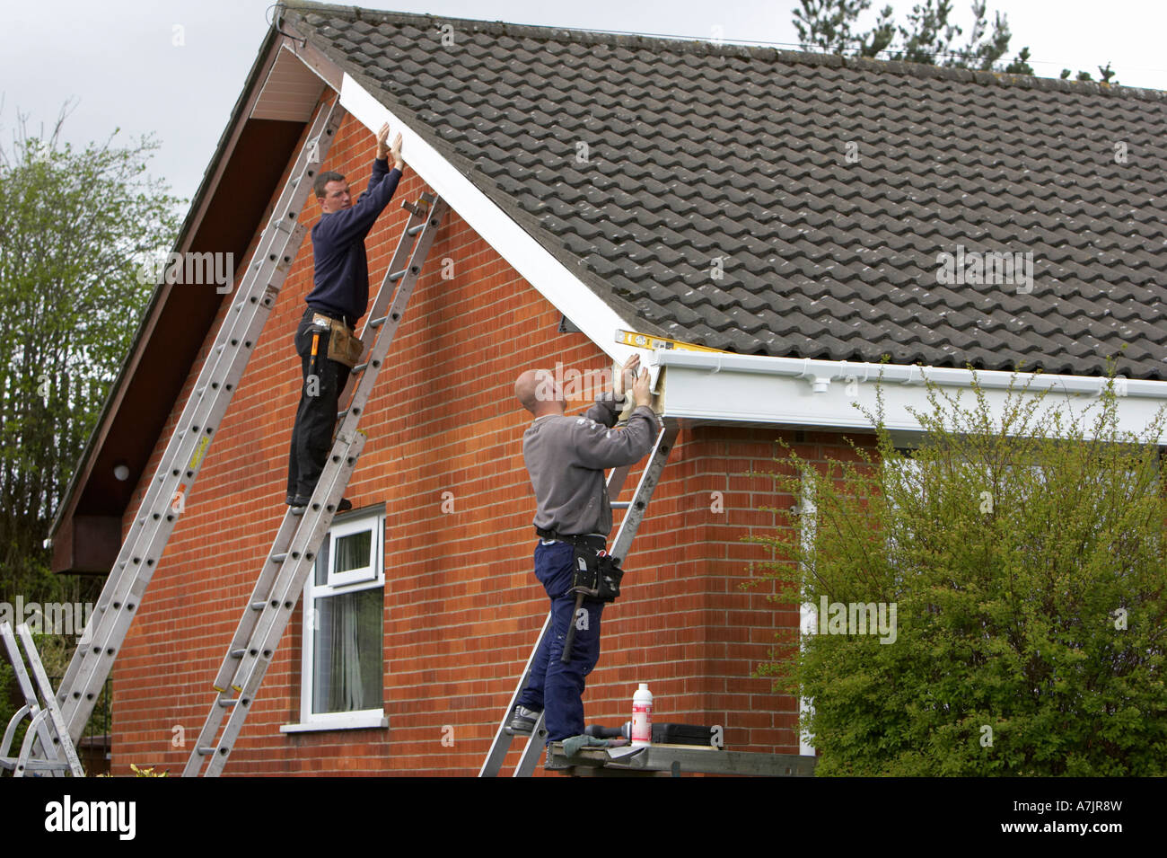 Workmen At The Top Of Ladders Installing White Pvc Cladding Over Old Wooden Panels On A Red Brick Bungalow