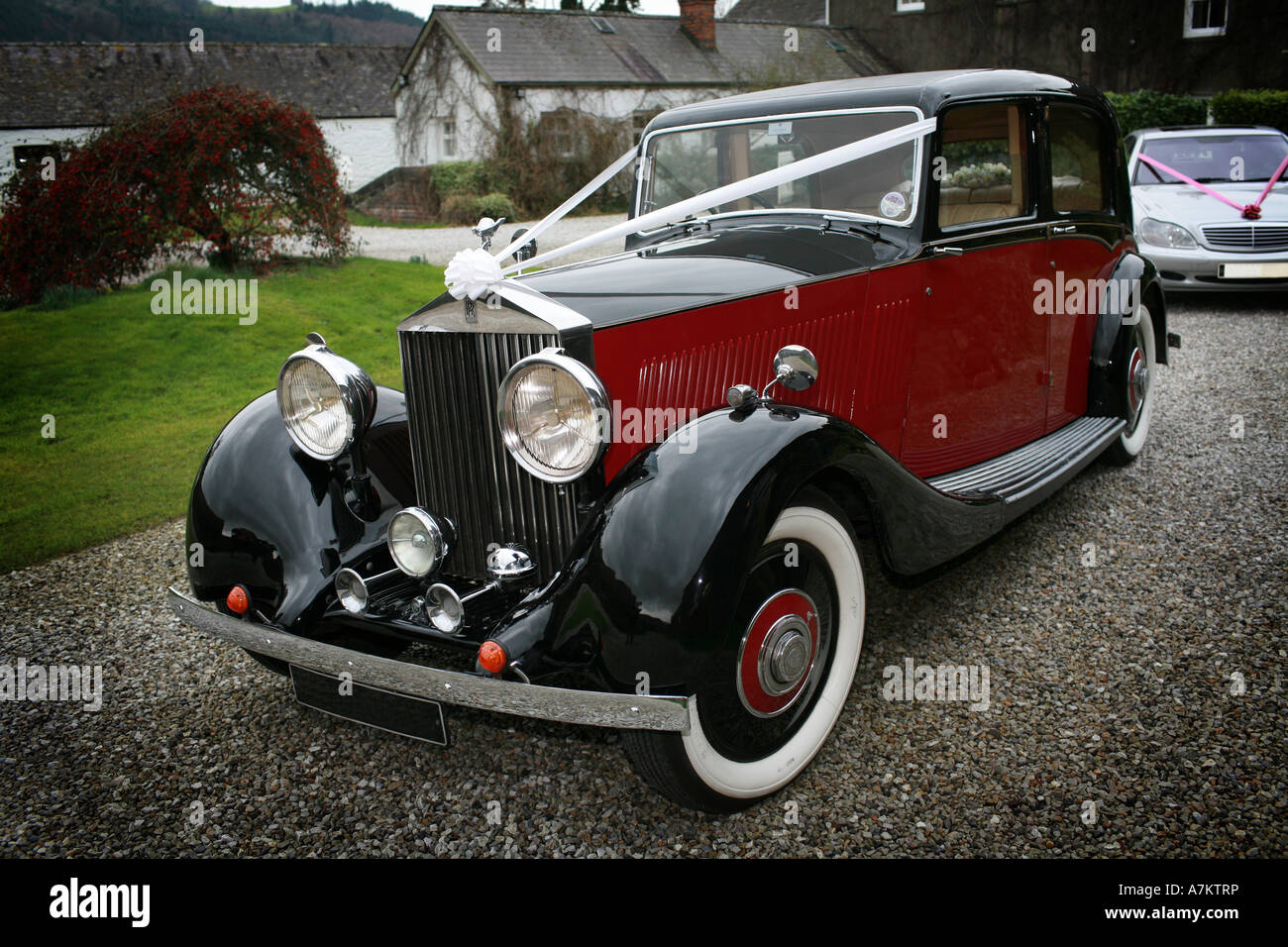 Red and black vintage Rolls Royce wedding car with typical white ...