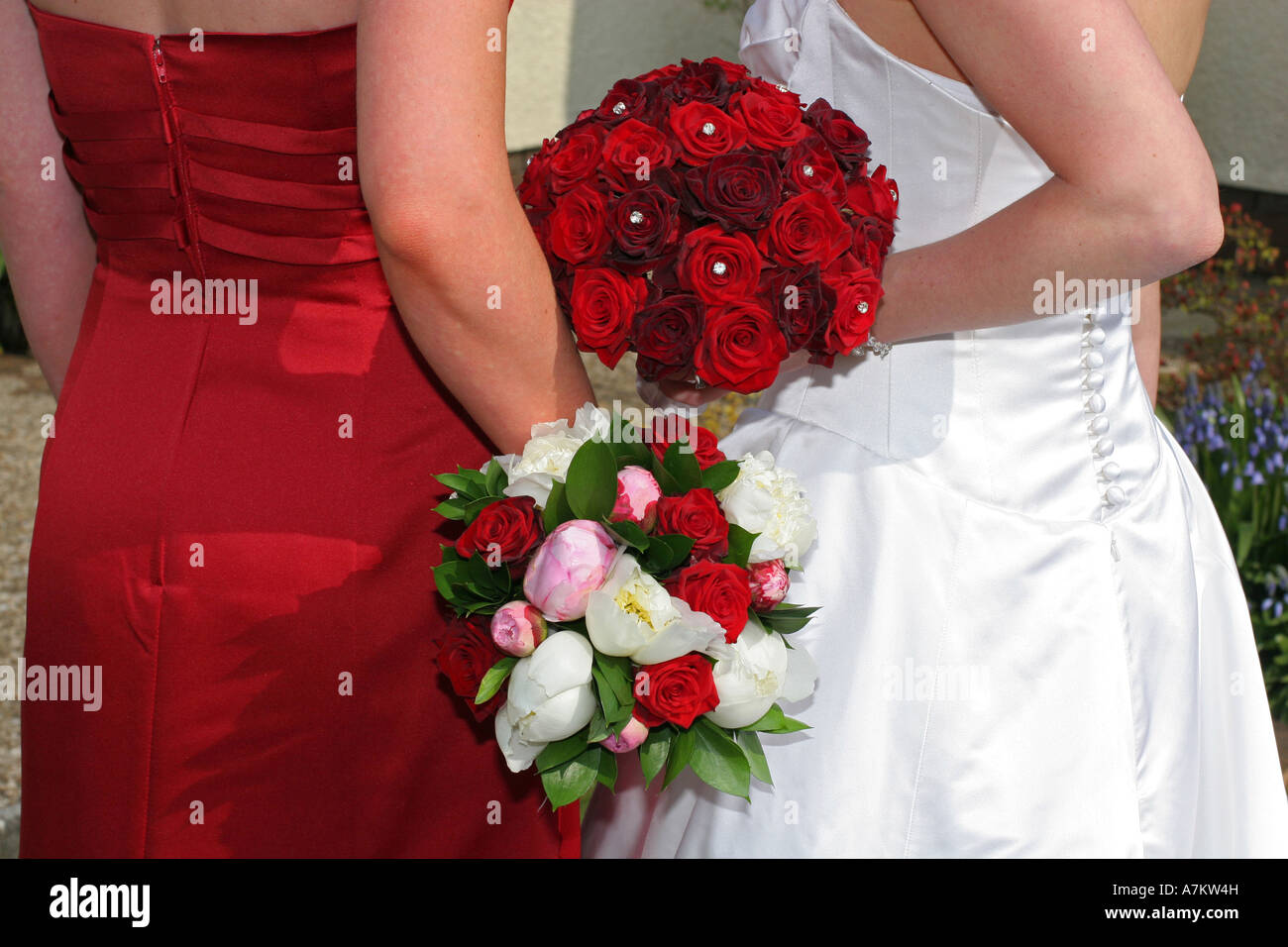 A Bride In White Wedding Dress Holds Red Rose Flower Bouquet On Top Of Bridesmaids Colourful Flowers Day UK