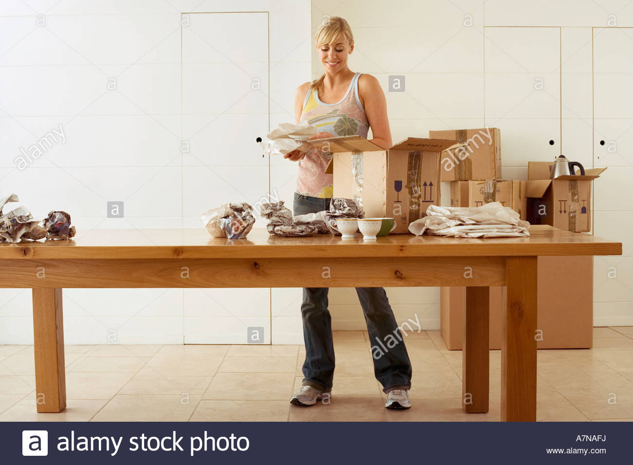 Dining room front view - Stock Photo Woman Moving House Packing Crockery In Cardboard Boxes On Dining Room Table Smiling Front View