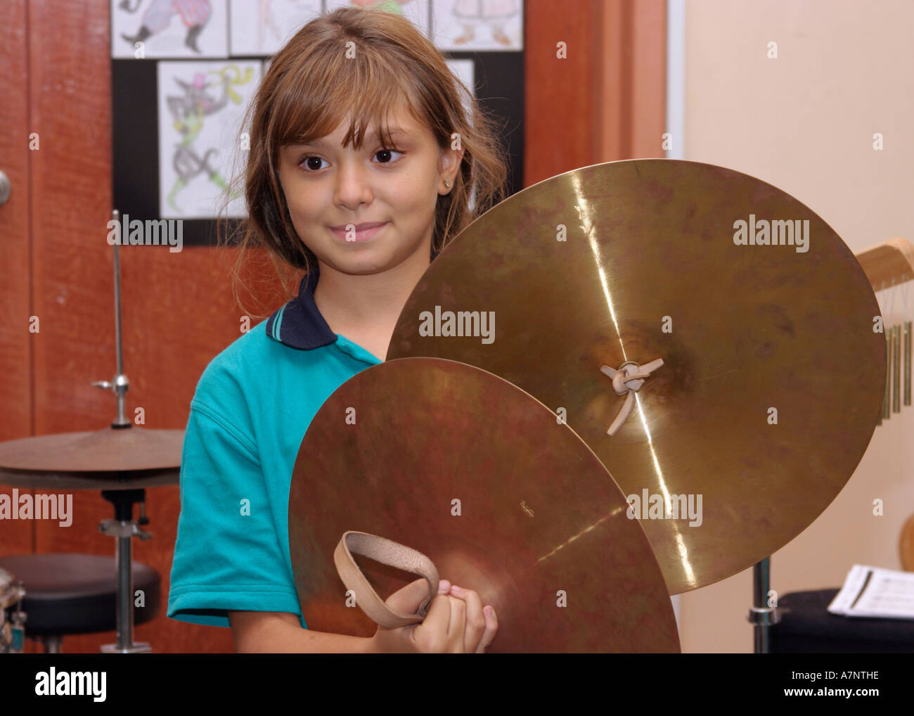 Stock Photo - young girl playing cymbals in music lesson at school