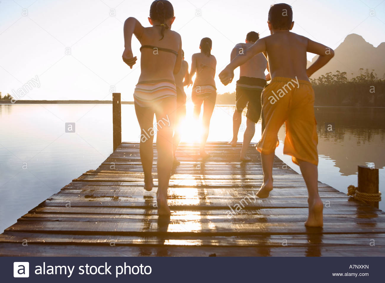 Kids Swimming In A Lake family in swimwear running along jetty jumping into lake at sunset