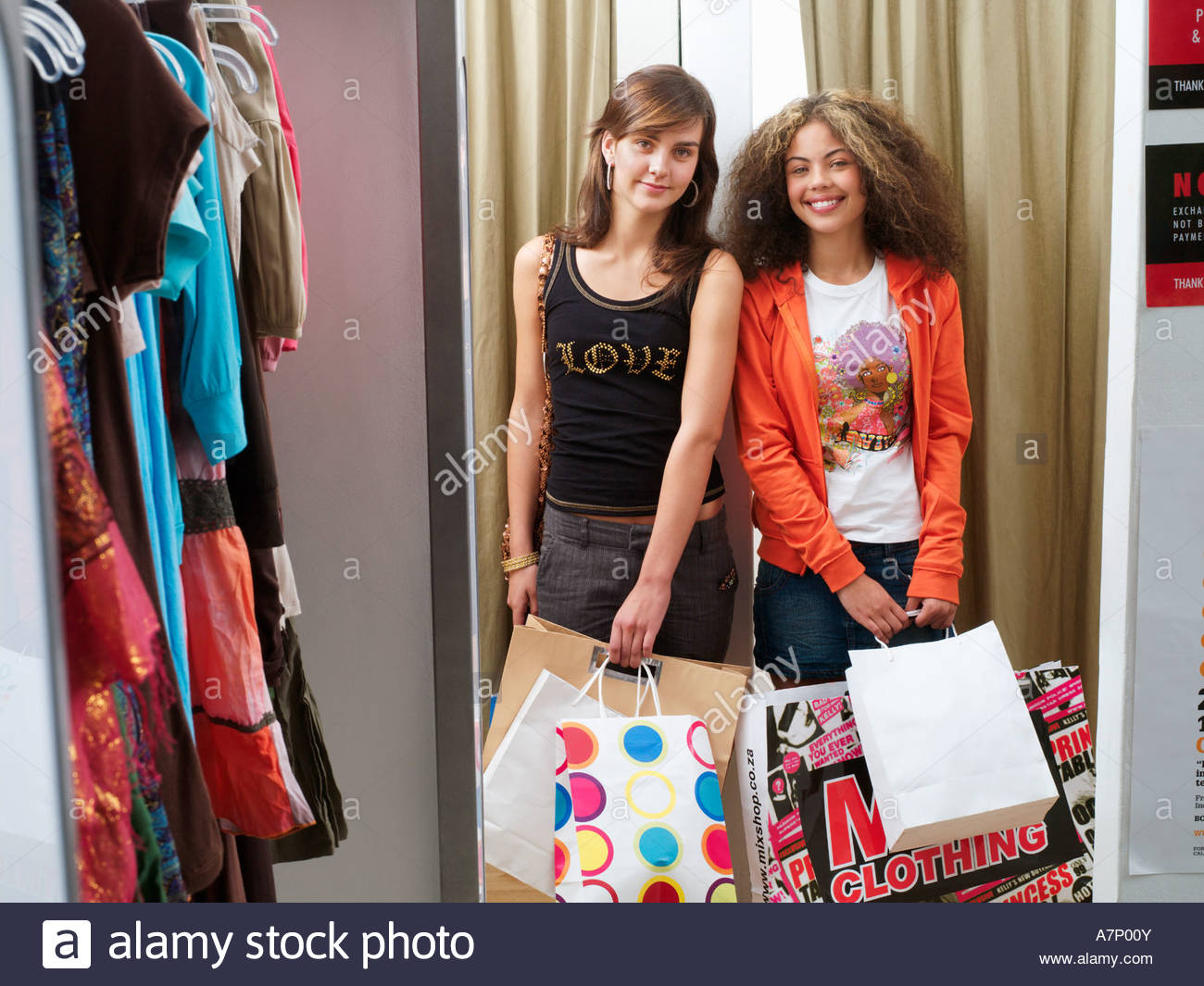 Two teenage girls 14 16 standing near fitting room in clothes shop ...