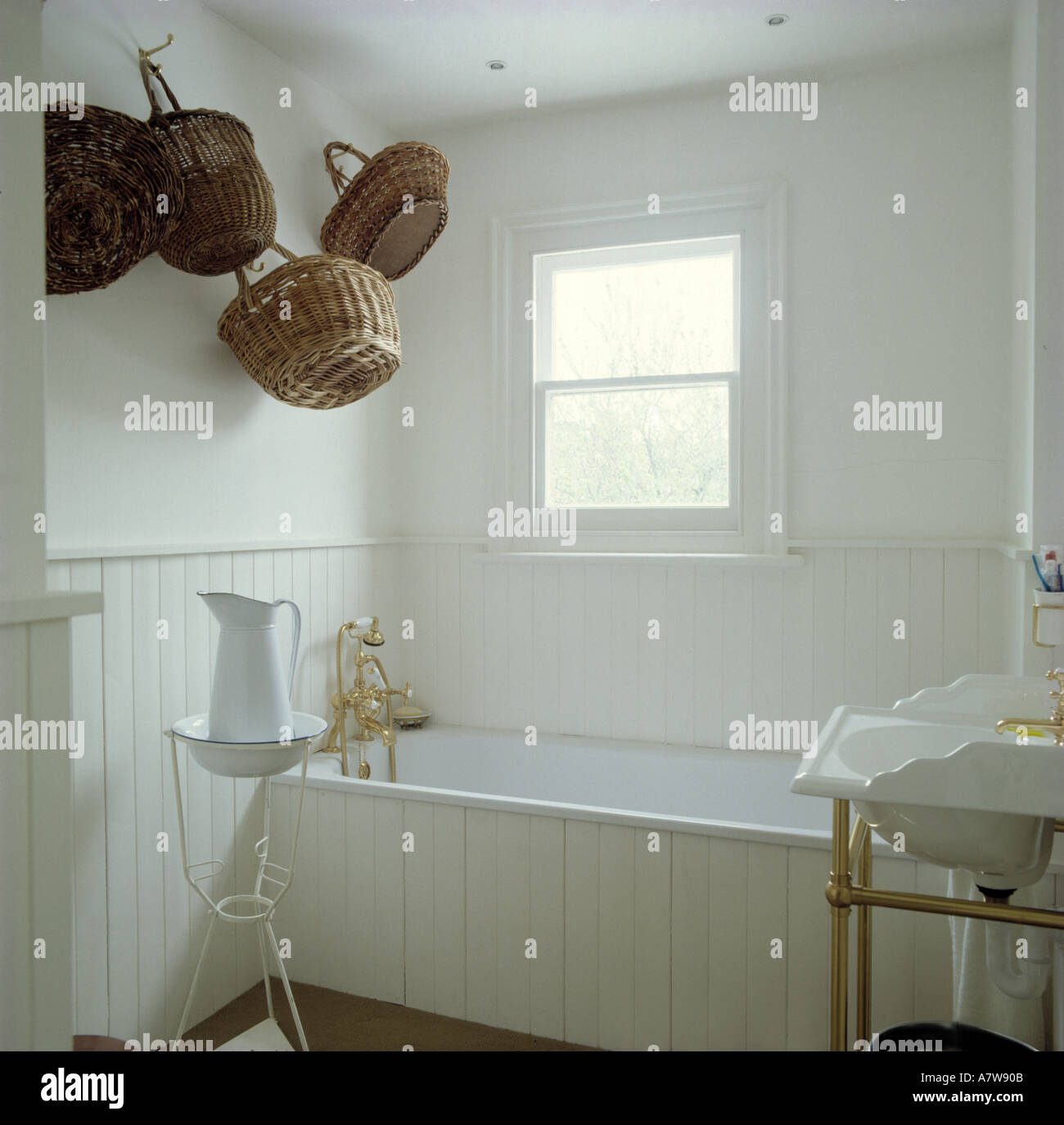 Collection of baskets on wall in white tongue groove panelling in simple  white bathroom with panelled bath. Collection of baskets on wall in white tongue groove panelling in